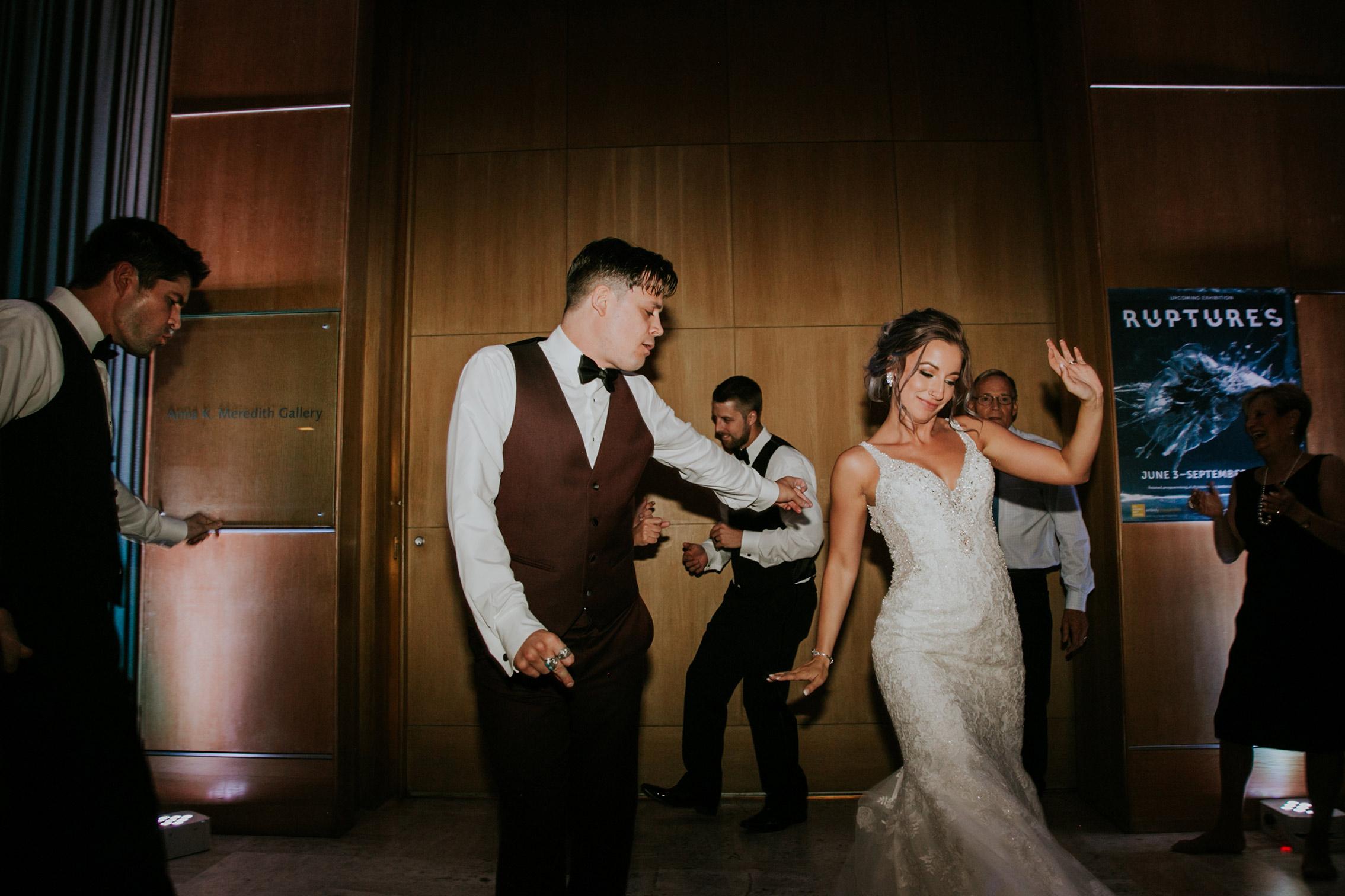 bride-groom-getting-down-next-to-eachother-on-dance-floor-desmoines-iowa-art-center-raelyn-ramey-photography.jpg
