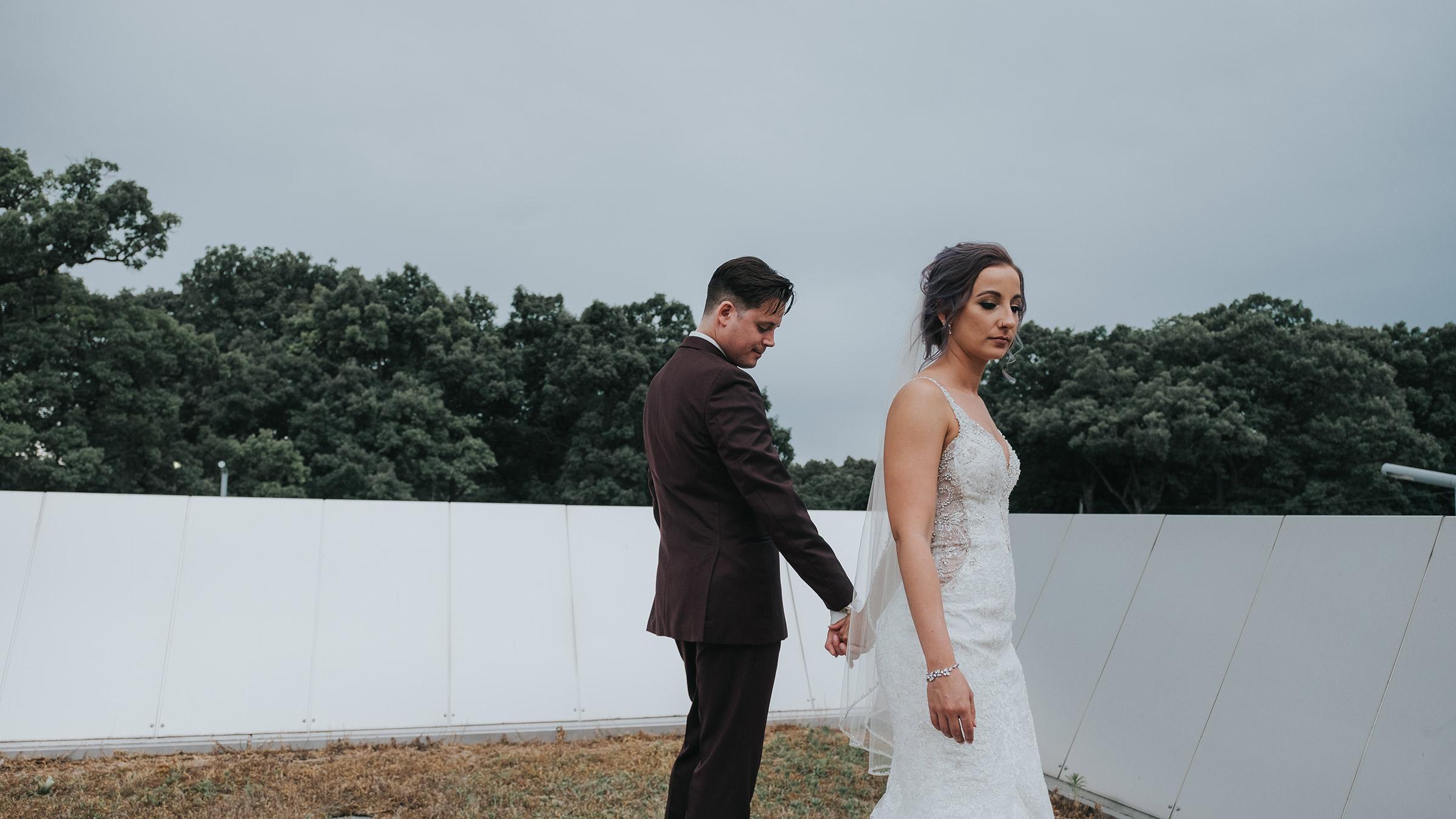 bride-groom-holding-hands-walking-opposite-desmoines-iowa-art-center-raelyn-ramey-photography.jpg