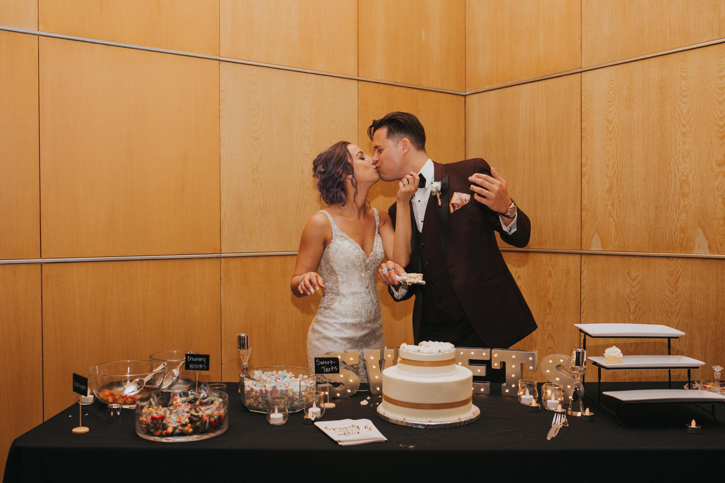 bride-groom-kissing-after-cake-cutting-desmoines-iowa-art-center-raelyn-ramey-photography.jpg