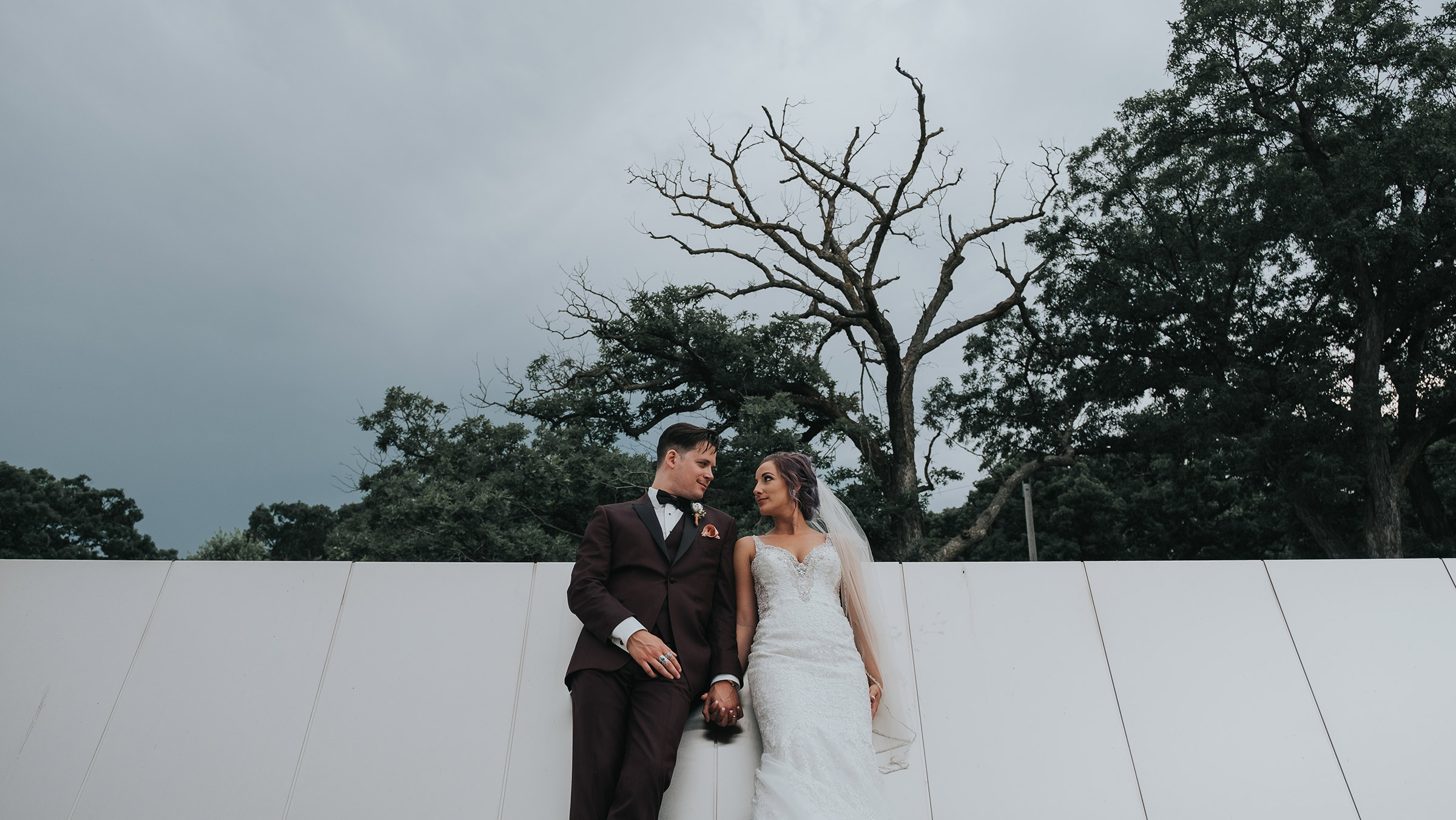 bride-groom-leaning-against-building-desmoines-iowa-art-center-raelyn-ramey-photography.jpg