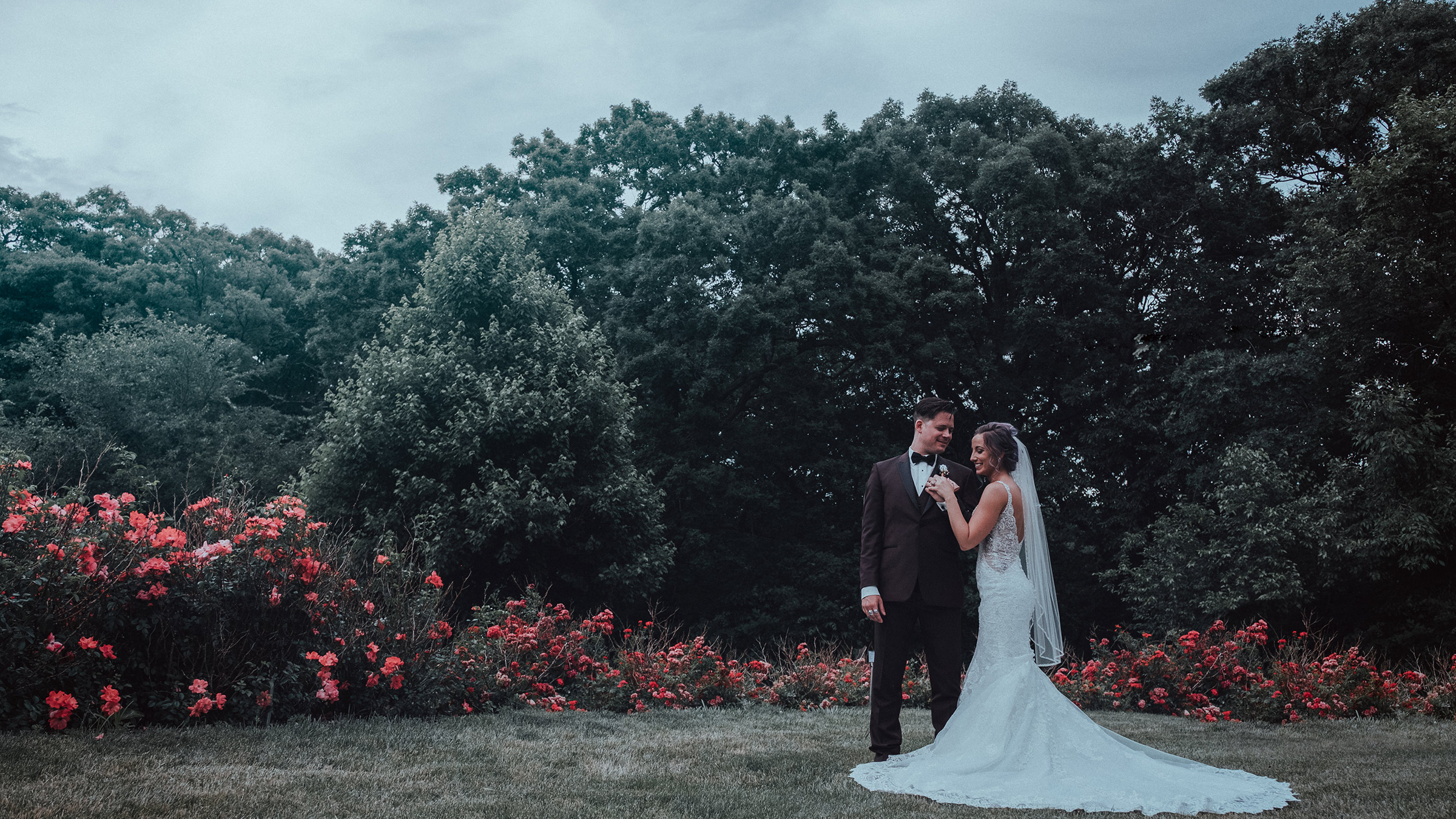 bride-groom-standing-in-rose-garden-holding-hands-desmoines-iowa-art-center-raelyn-ramey-photography.jpg