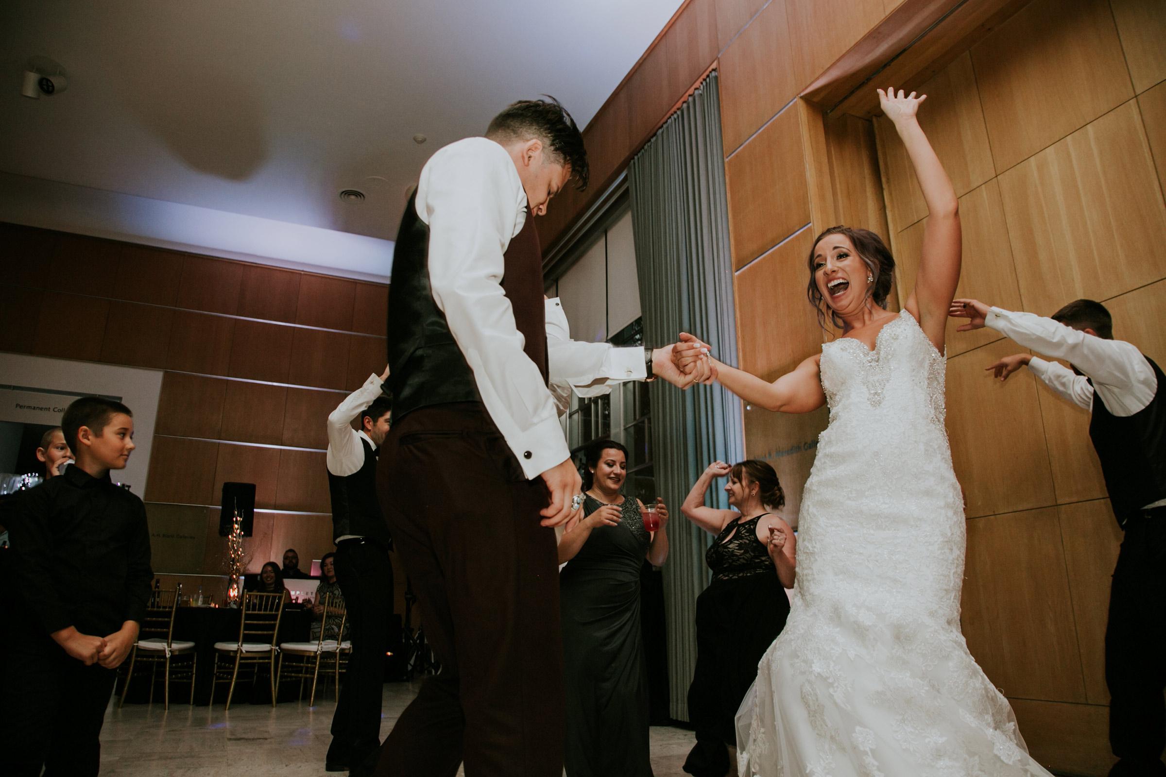 bride-groom-swinging-each-other-around-on-dance-floor-desmoines-iowa-art-center-raelyn-ramey-photography.jpg