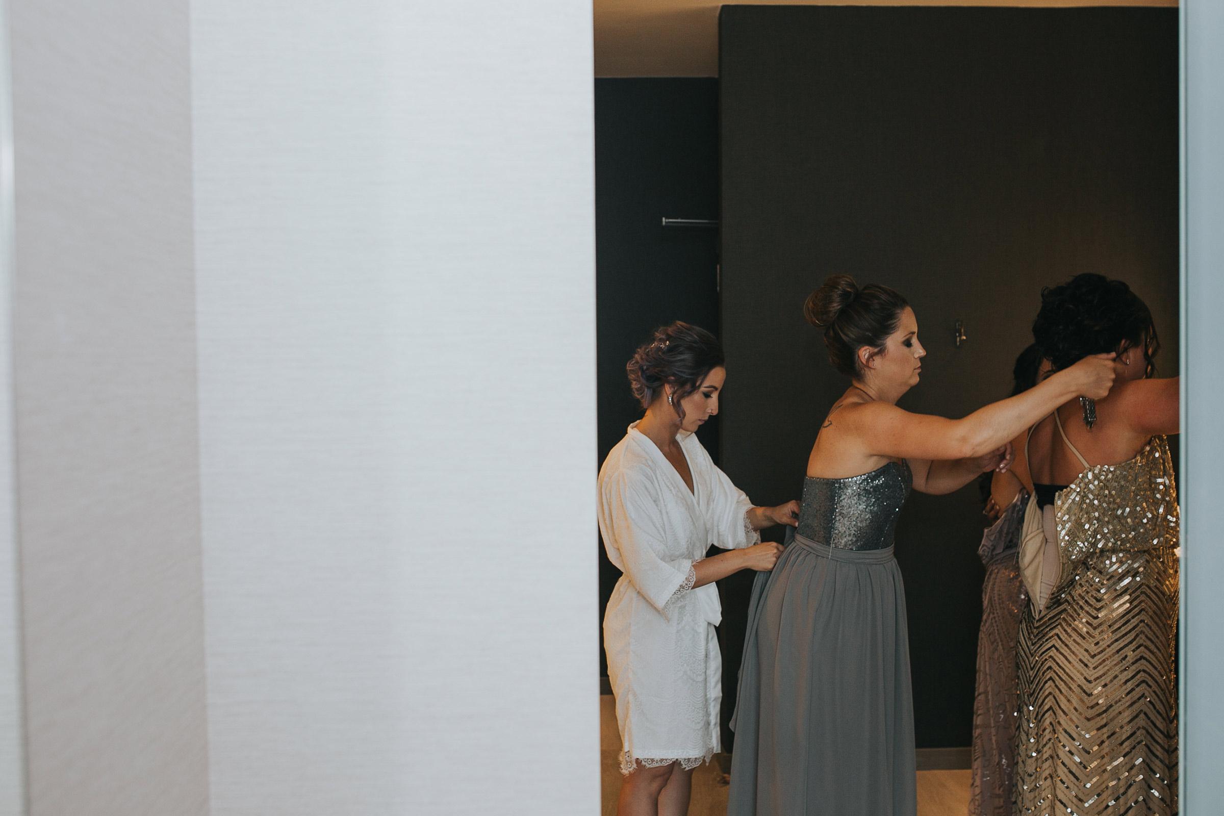 bride-helping-bridesmaids-get-ready-desmoines-iowa-ac-hotel-raelyn-ramey-photography.jpg