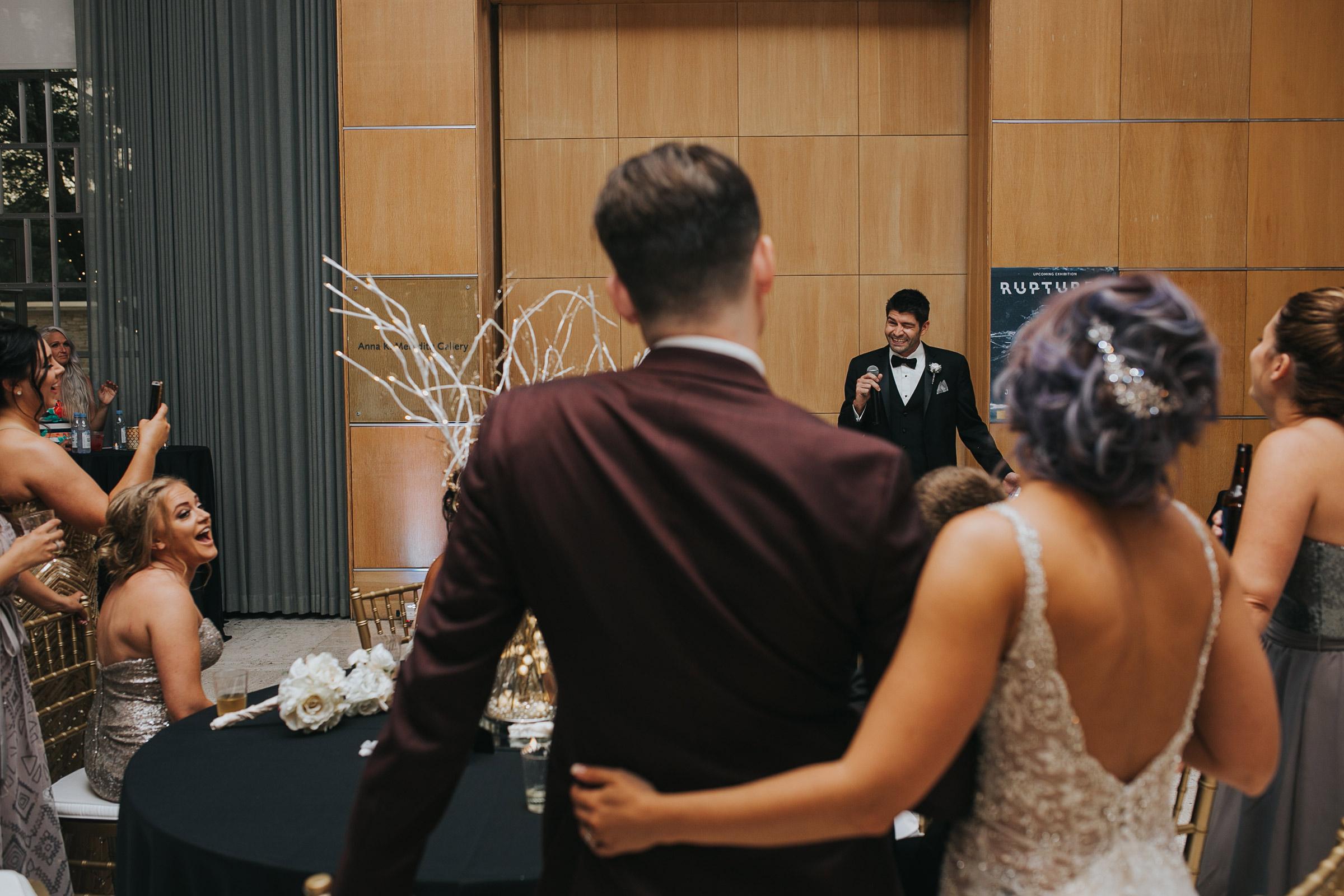 bride-groom-watching-best-man-make-speech-desmoines-iowa-art-center-raelyn-ramey-photography.jpg