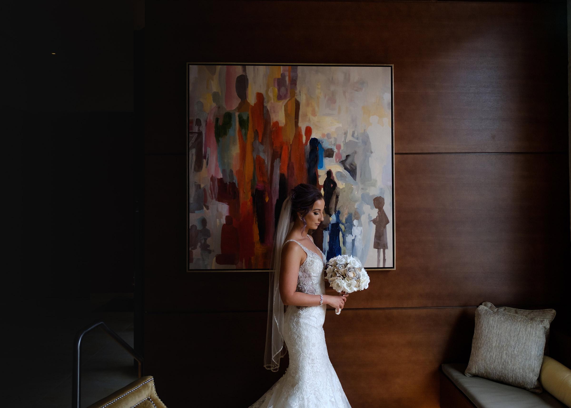 bride-in-front-of-lobby-artwork-desmoines-iowa-ac-hotel-raelyn-ramey-photography.jpg