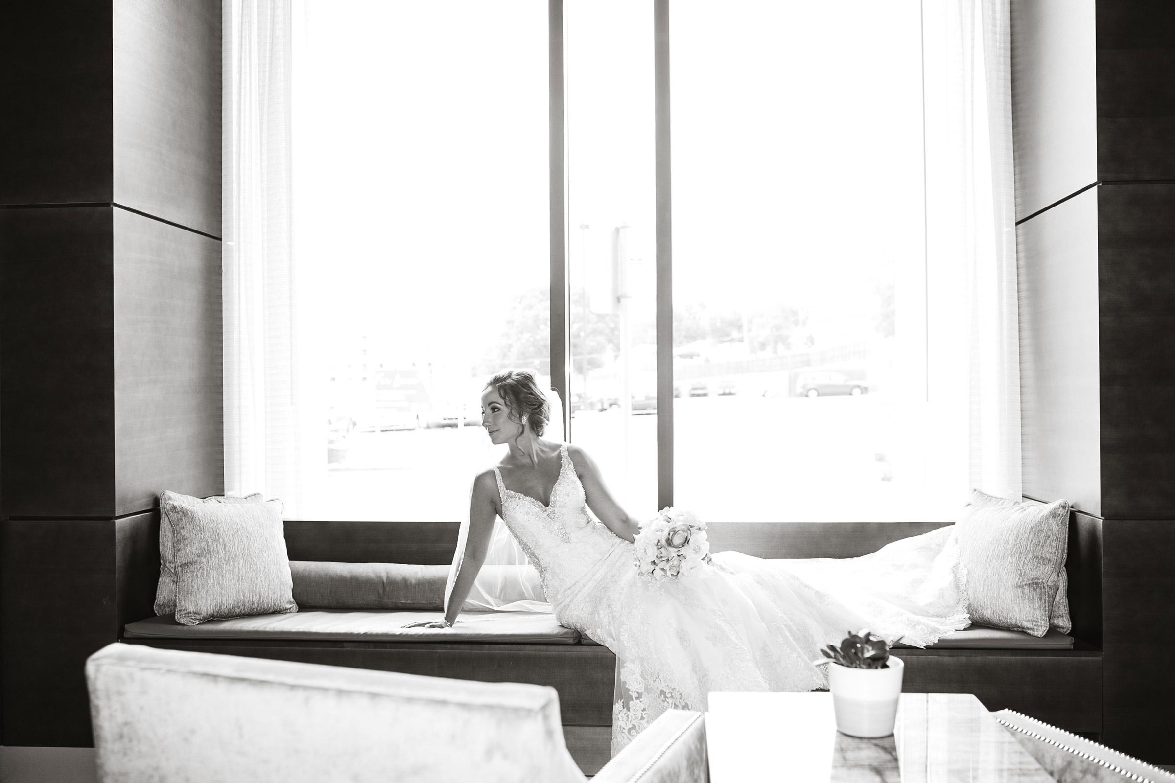 bride-posing-in-window-lobby-desmoines-iowa-ac-hotel-raelyn-ramey-photography.jpg
