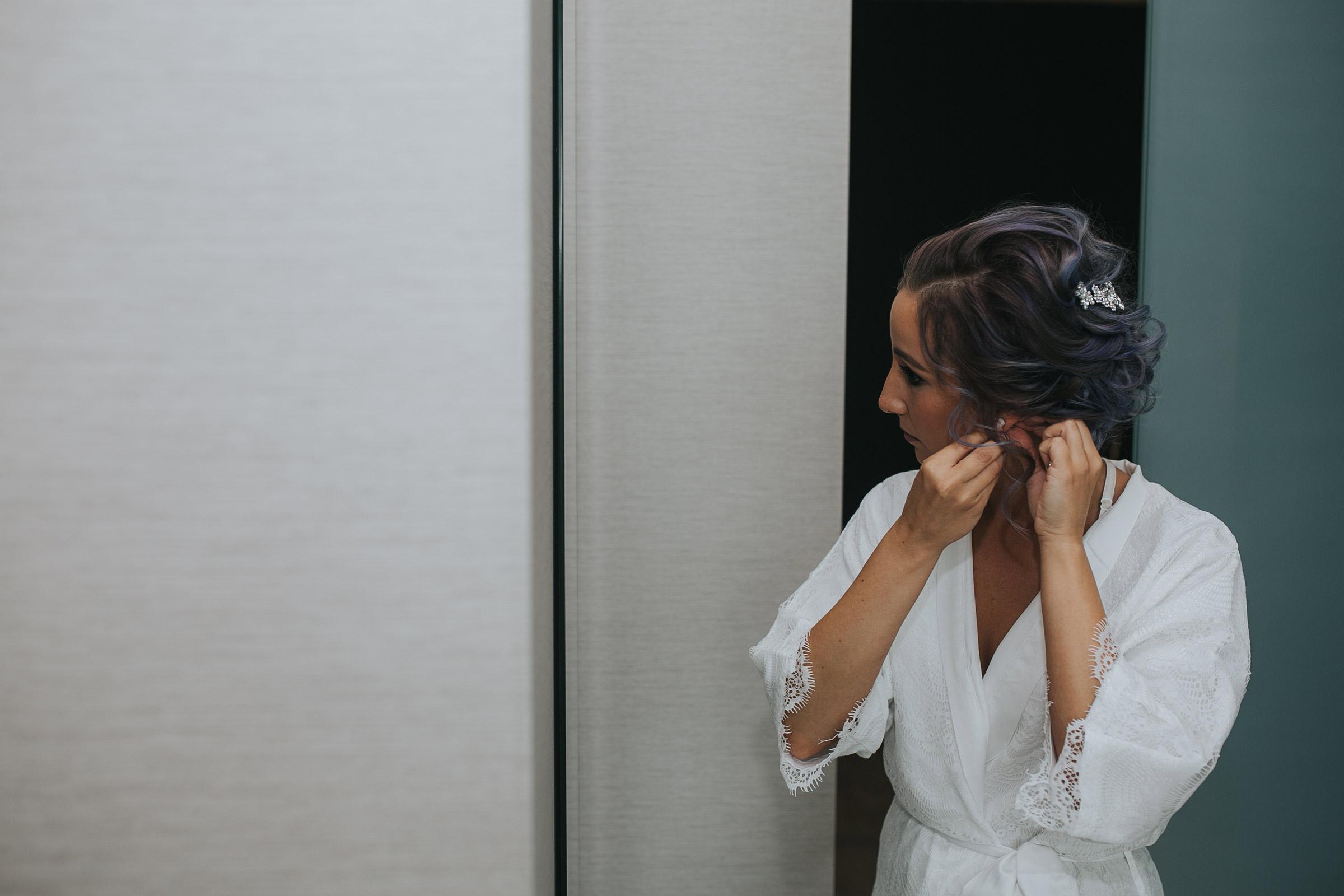 bride-putting-earings-on-desmoines-iowa-ac-hotel-raelyn-ramey-photography.jpg