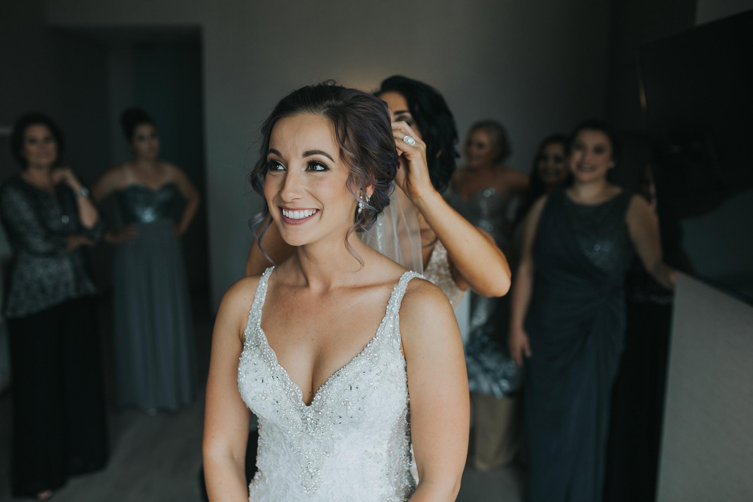 bride-putting-veil-on-with-bridesmaid-desmoines-iowa-ac-hotel-raelyn-ramey-photography.jpg