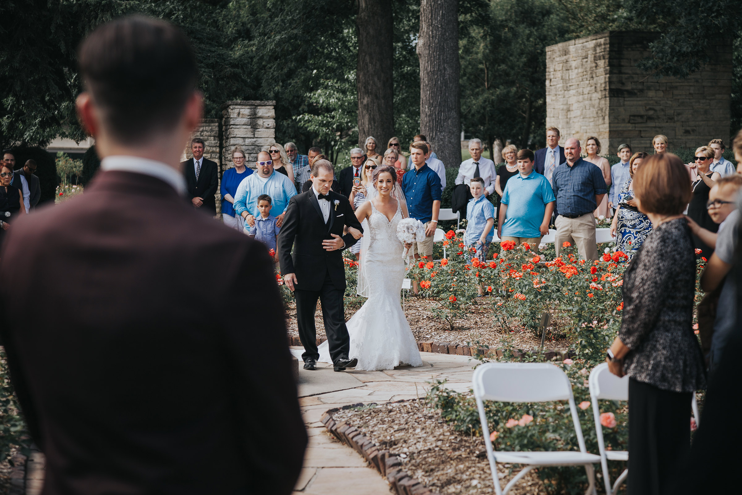 bride-walking-down-aisle-with-dad-to-groom-during-ceremony-desmoines-iowa-rose-garden-raelyn-ramey-photography.jpg