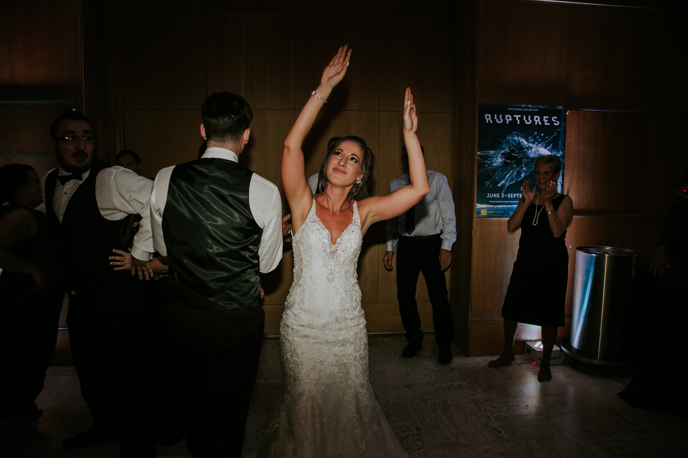 bride-with-arms-in-the-air-dancing-on-floor-desmoines-iowa-art-center-raelyn-ramey-photography.jpg