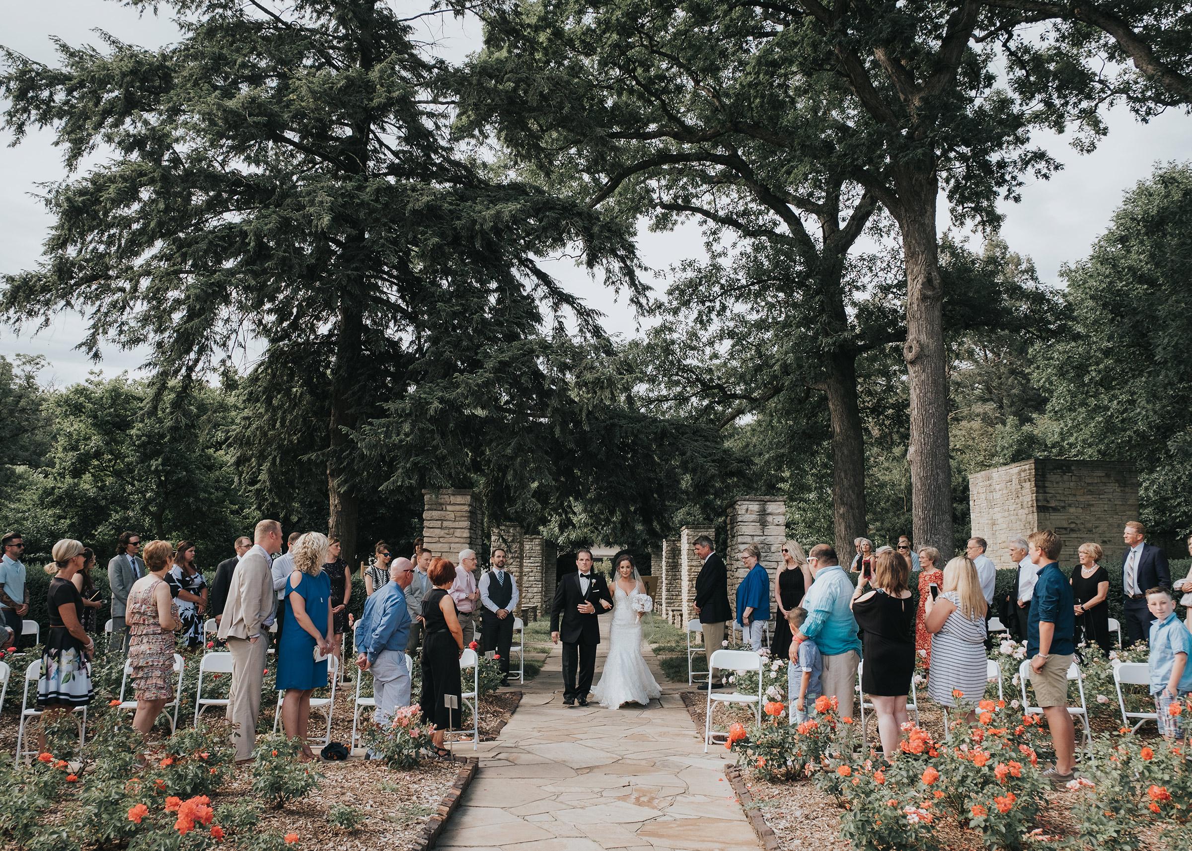 bride-walking-down-aisle-with-her-dad-desmoines-iowa-rose-garden-raelyn-ramey-photography.jpg