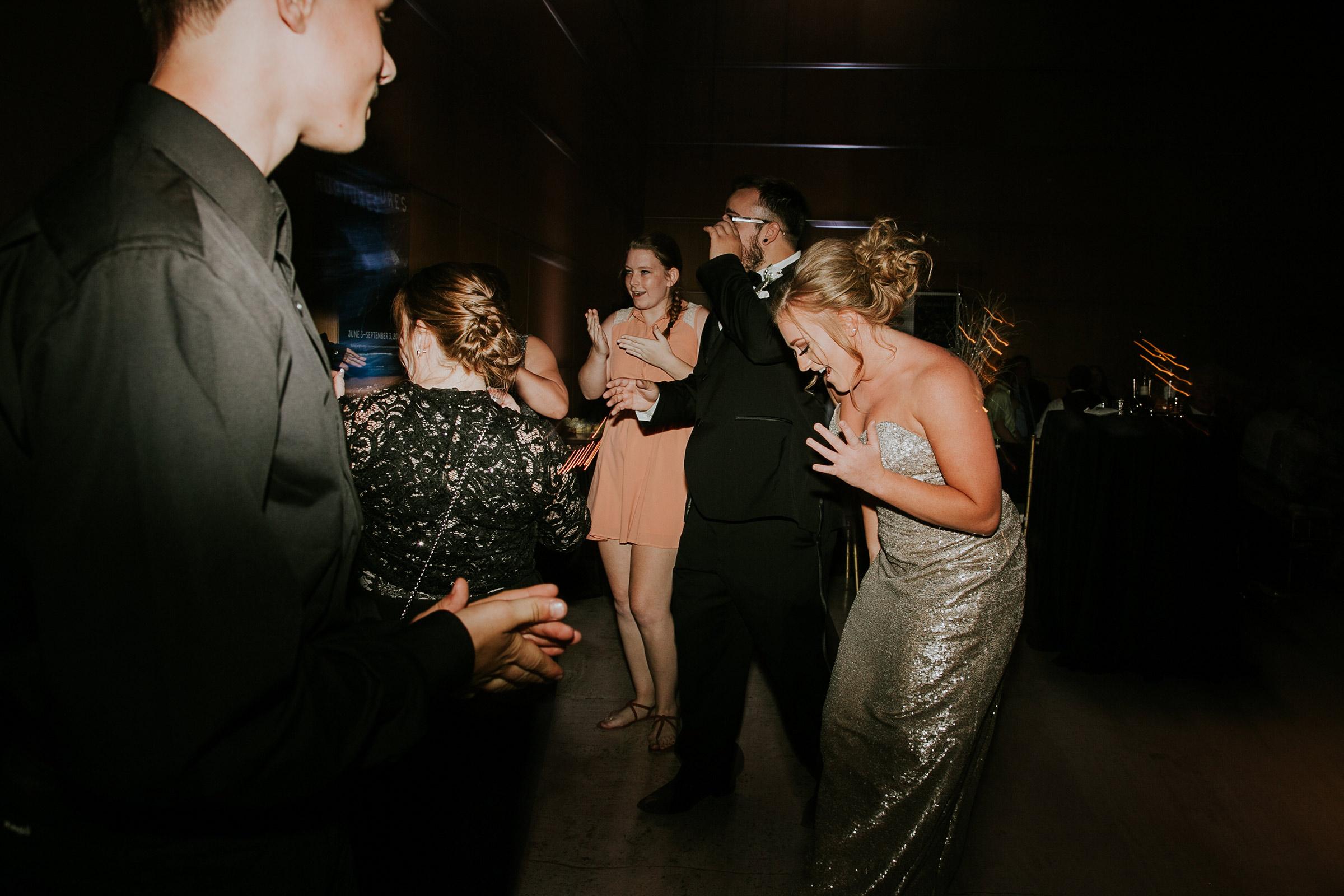 bridesmaid-dancing-with-guest-on-dance-floor-desmoines-iowa-art-center-raelyn-ramey-photography.jpg