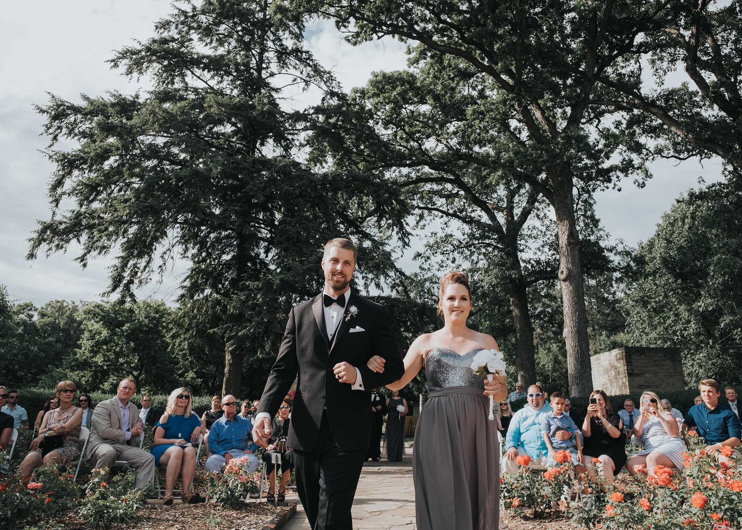 bridesmaid-and-groomsmen-smiling-walking-down-aisle-desmoines-iowa-rose-garden-raelyn-ramey-photography.jpg