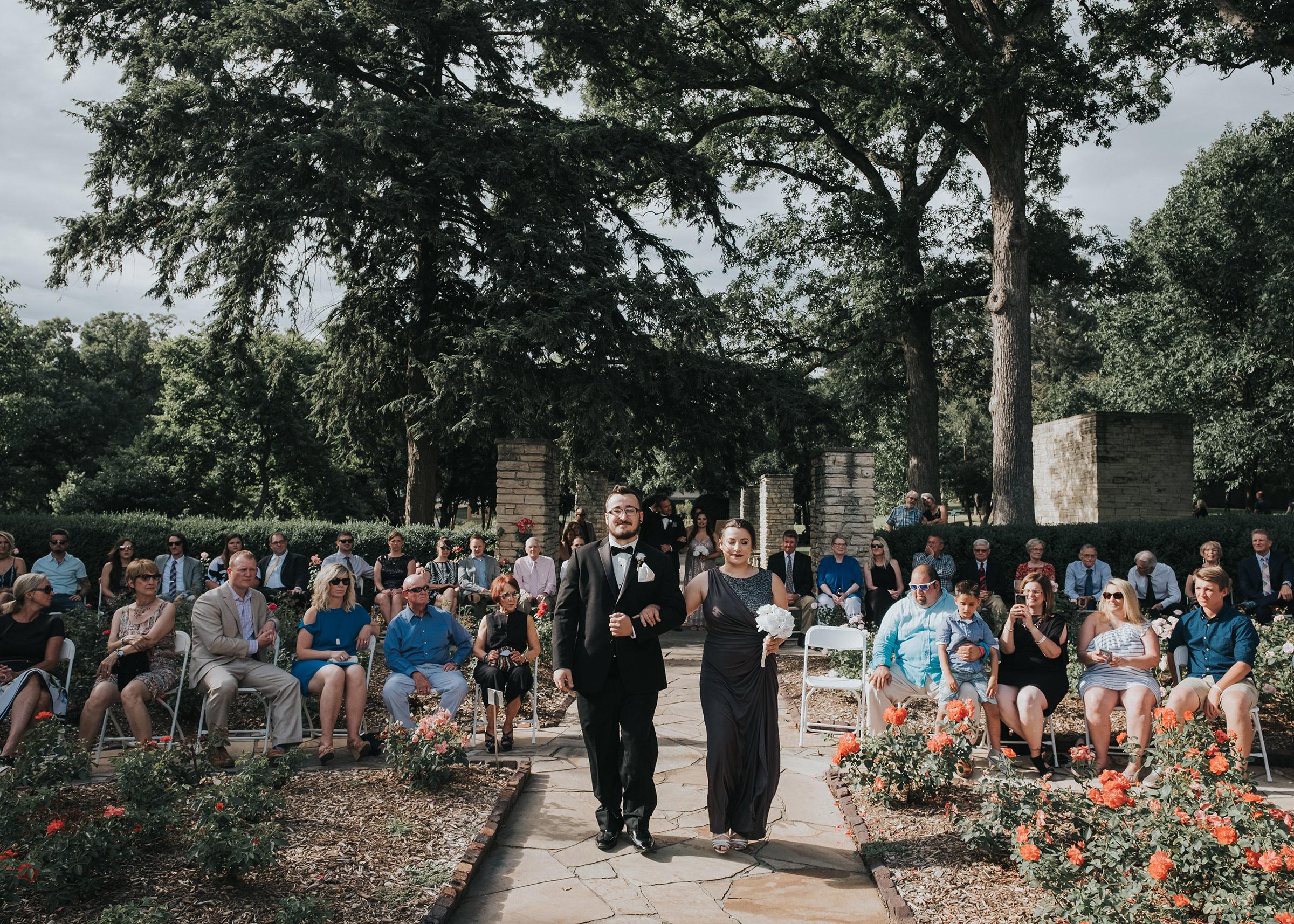 bridesmaid-groomsmen-walking-down-aisle-during-ceremony-desmoines-iowa-rose-garden-raelyn-ramey-photography.jpg
