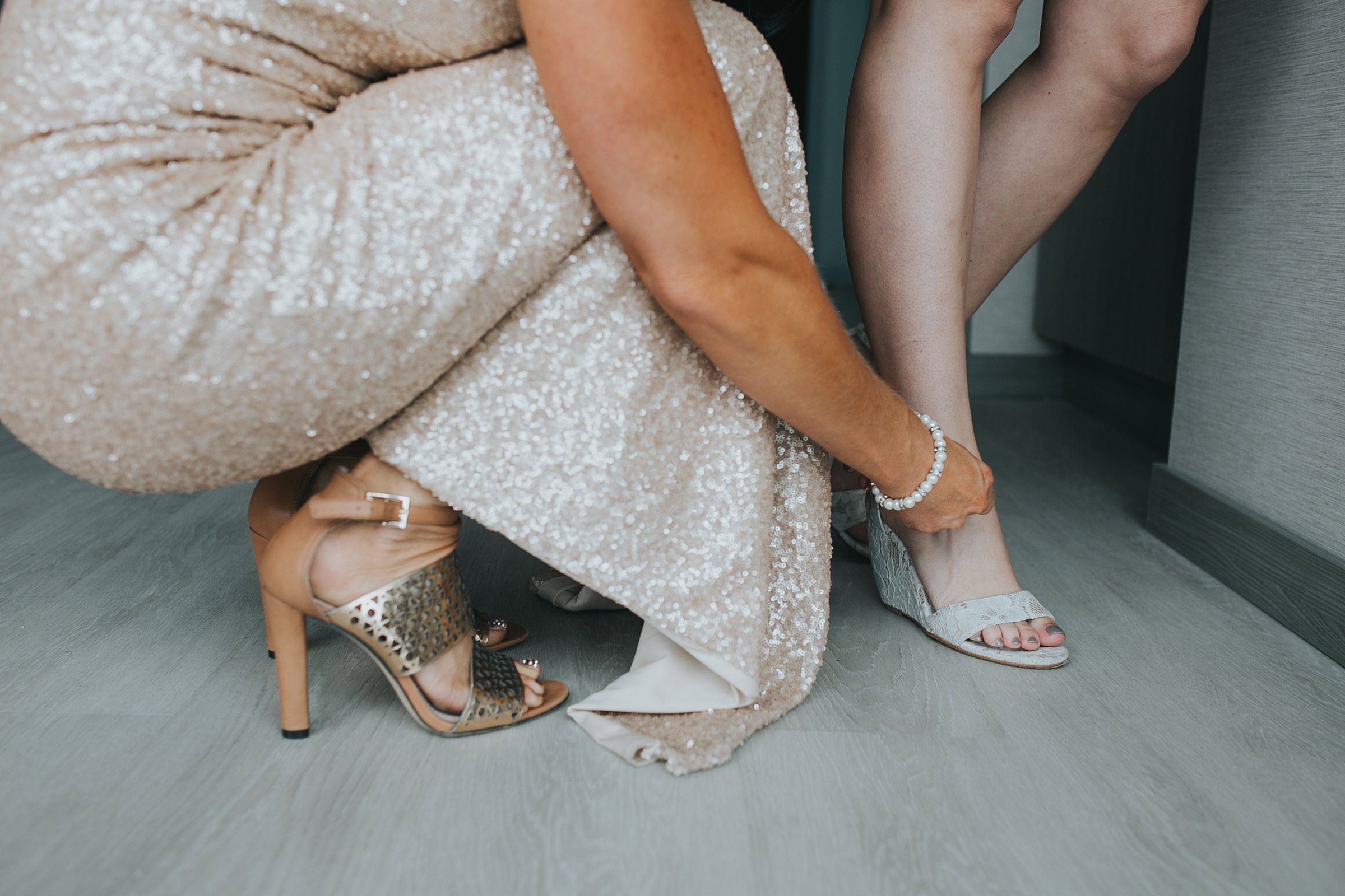 bridesmaid-helping-bride-put-shoes-on-desmoines-iowa-ac-hotel-raelyn-ramey-photography.jpg