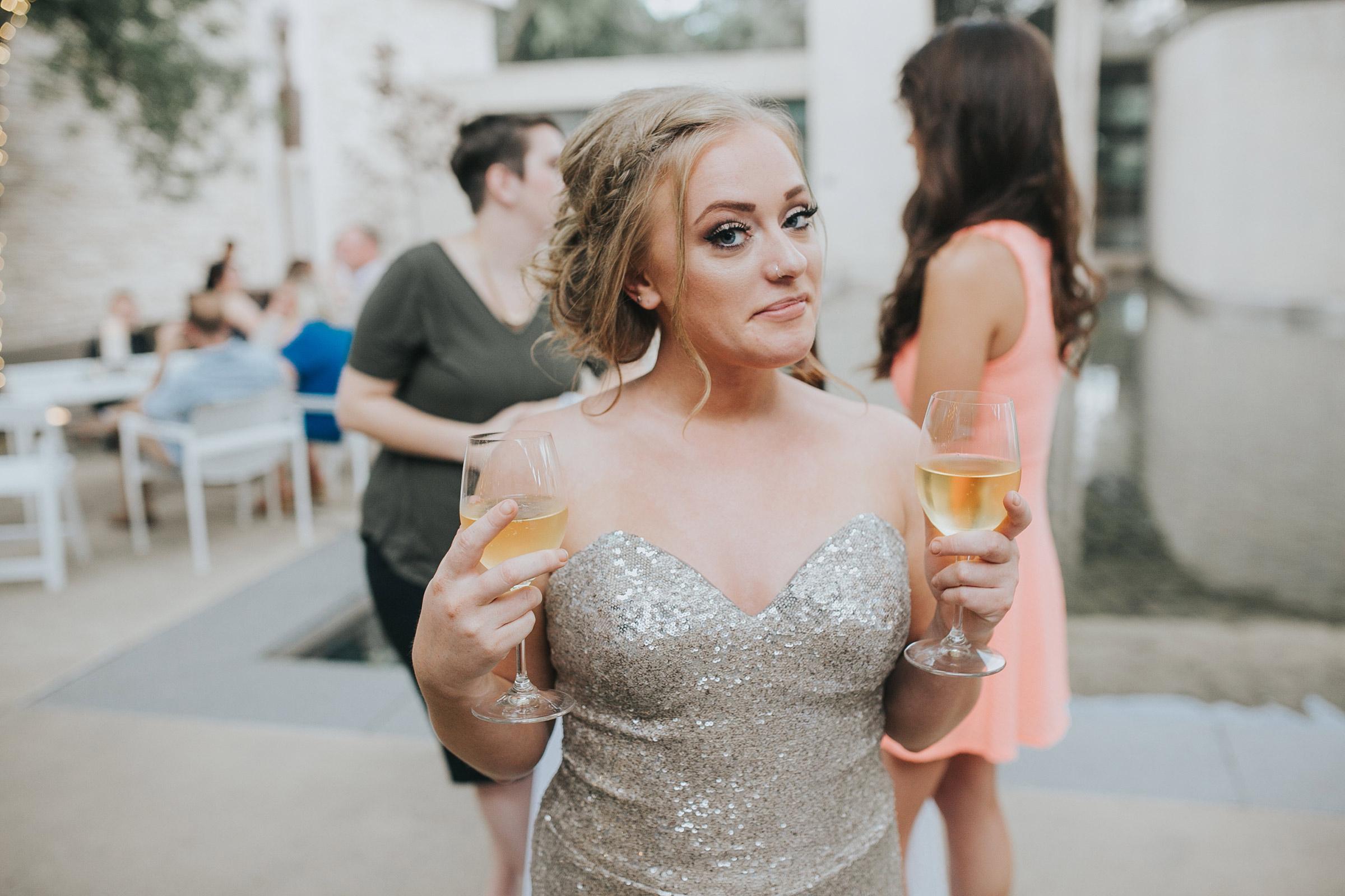 bridesmaid-holding-two-drinks-desmoines-iowa-art-center-raelyn-ramey-photography.jpg