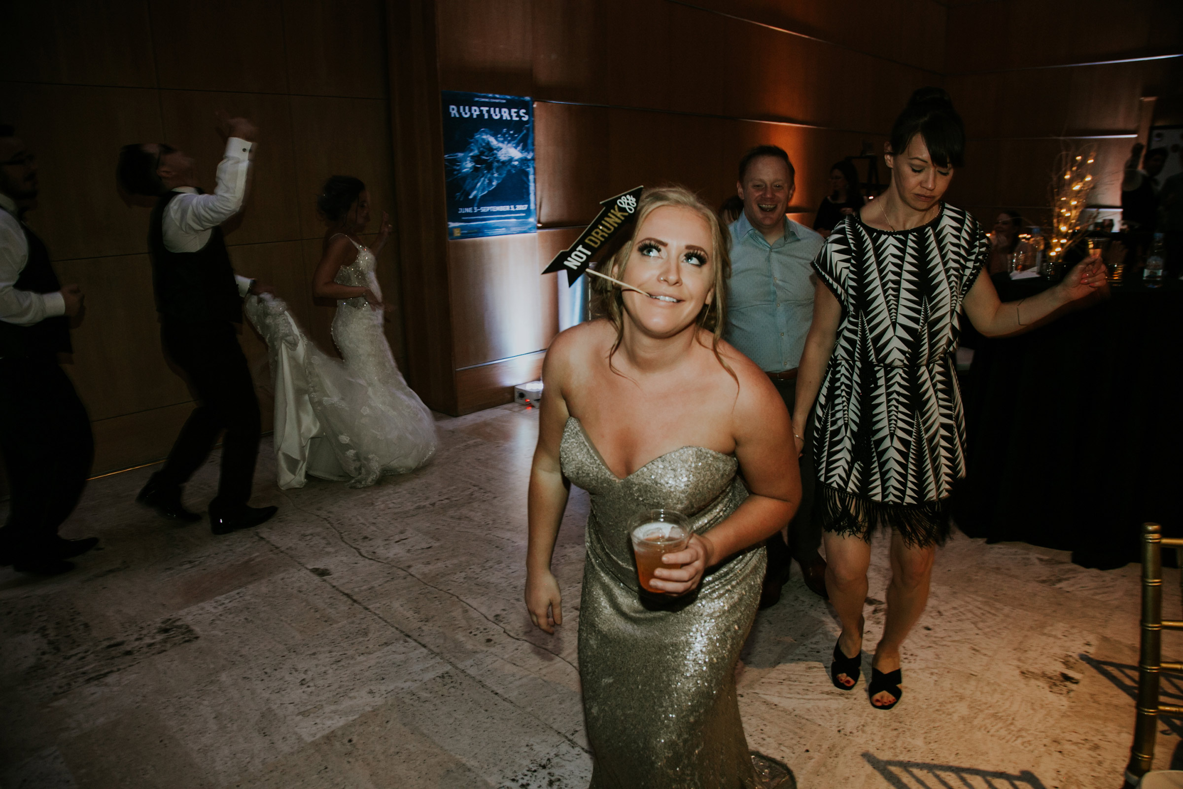bridesmaid-holding-drunk-sign-in-mouth-on-the-dance-floor-after-hours-desmoines-iowa-art-center-raelyn-ramey-photography.jpg