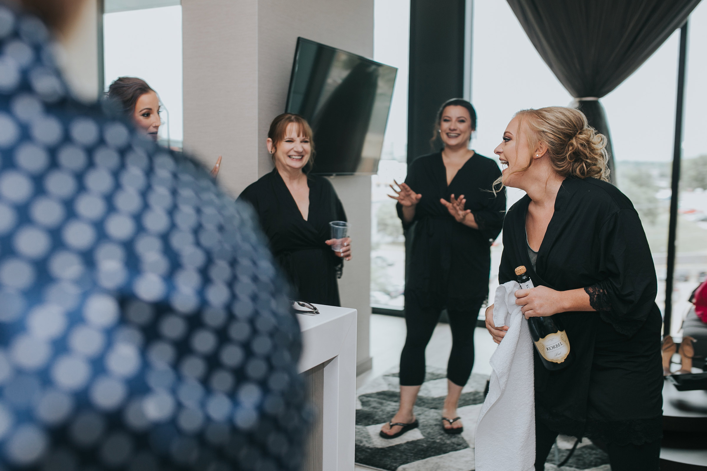 bridesmaid-opening-champagne-desmoines-iowa-ac-hotel-raelyn-ramey-photography.jpg