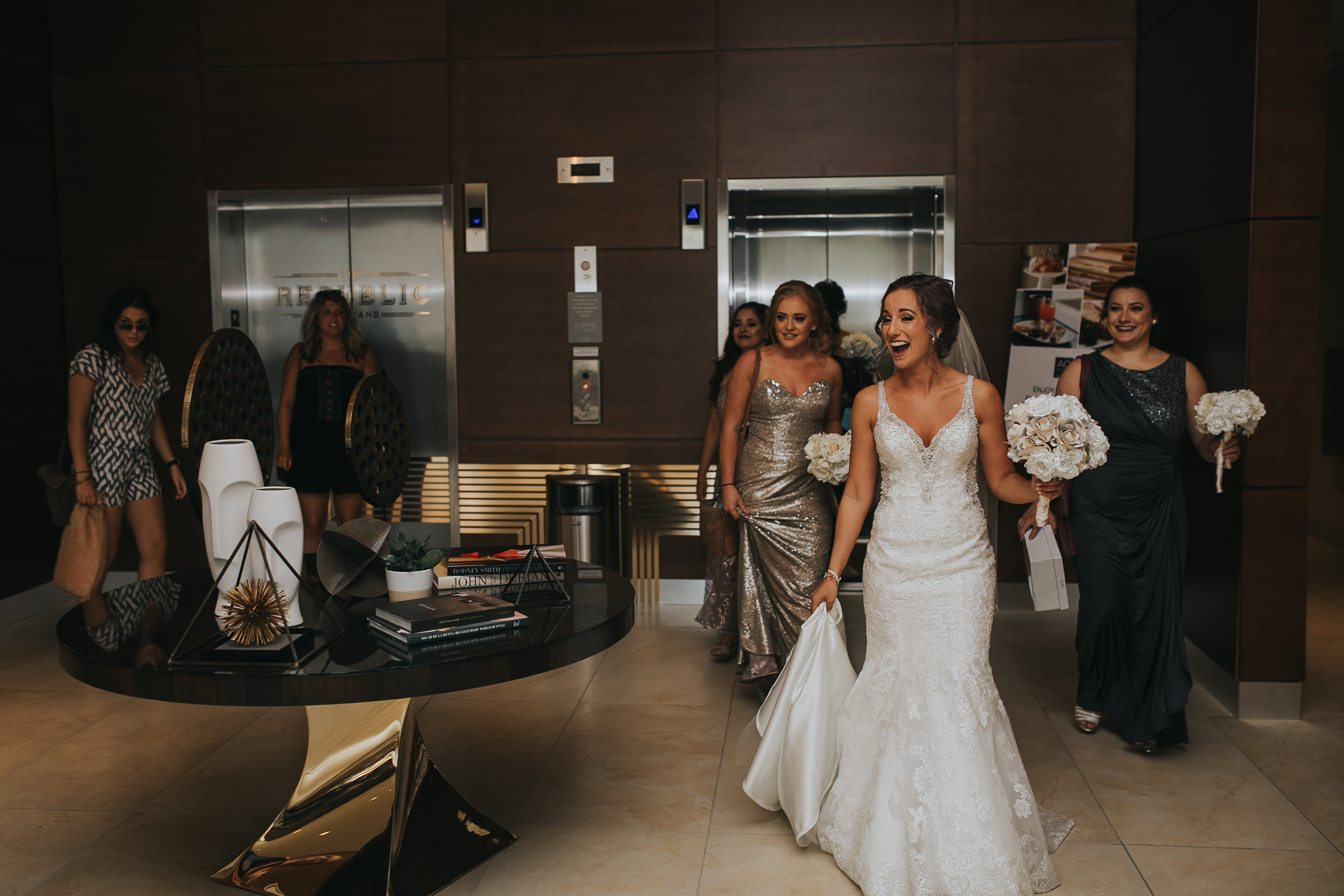 bridesmaids-and-bride-coming-off-elevators-in-lobby-desmoines-iowa-ac-hotel-raelyn-ramey-photography.jpg