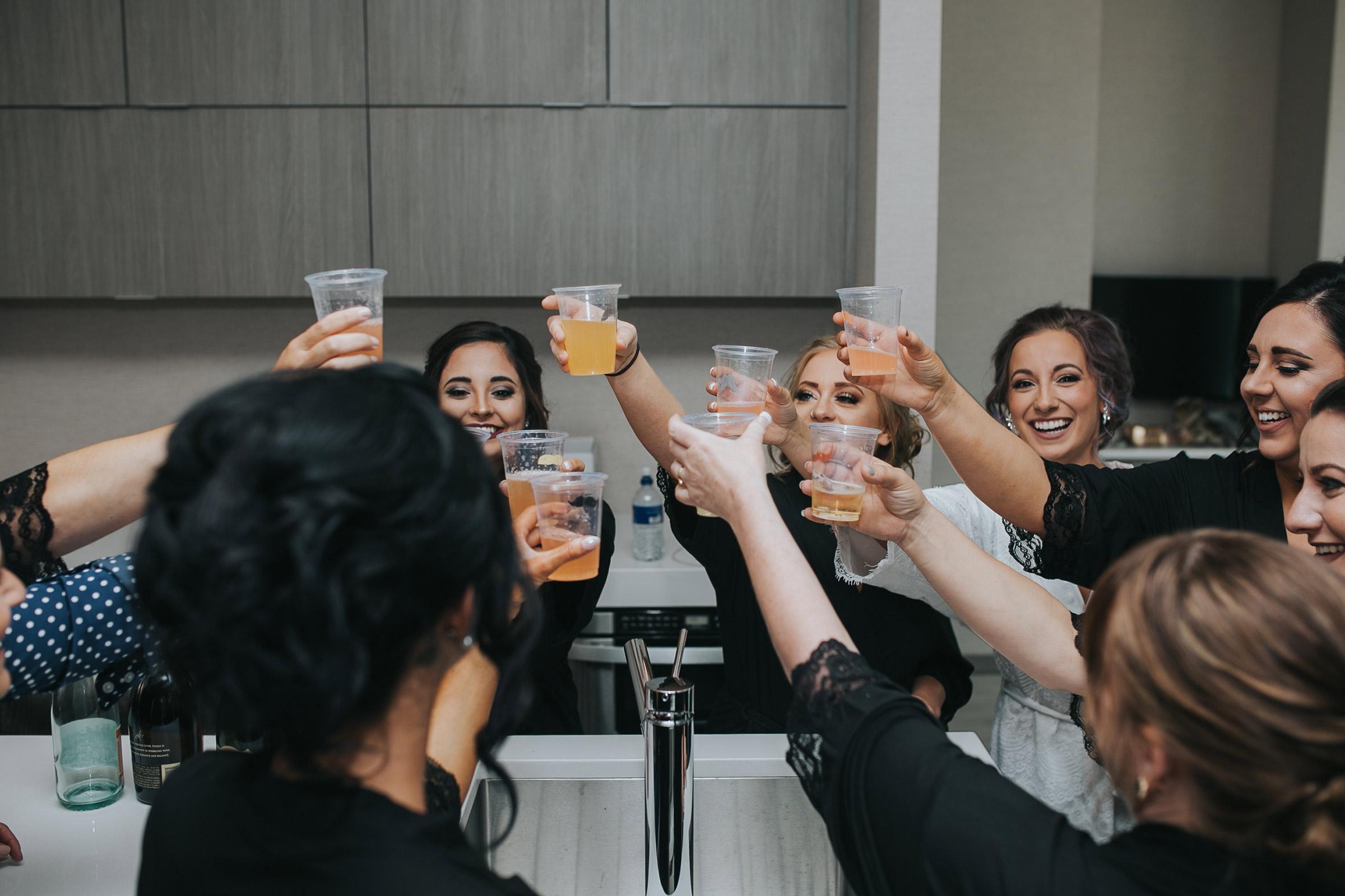 bridesmaids-cheers-before-getting-ready-desmoines-iowa-ac-hotel-raelyn-ramey-photography.jpg