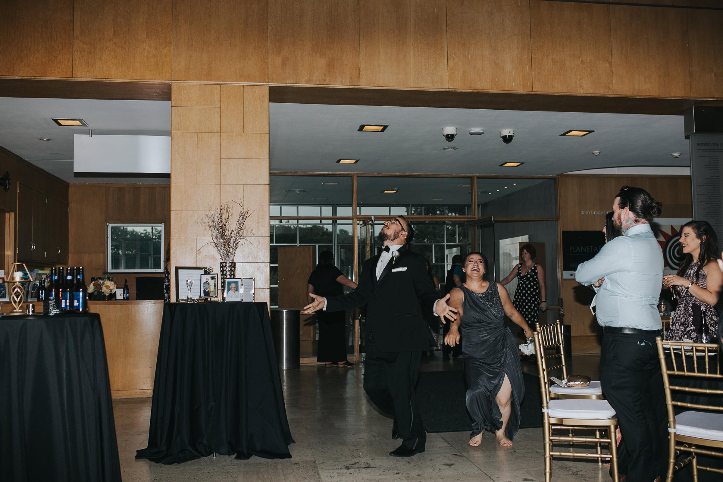 bridesmaids-and-groomsmen-grand-enterance-having-fun-desmoines-iowa-art-center-raelyn-ramey-photography.jpg