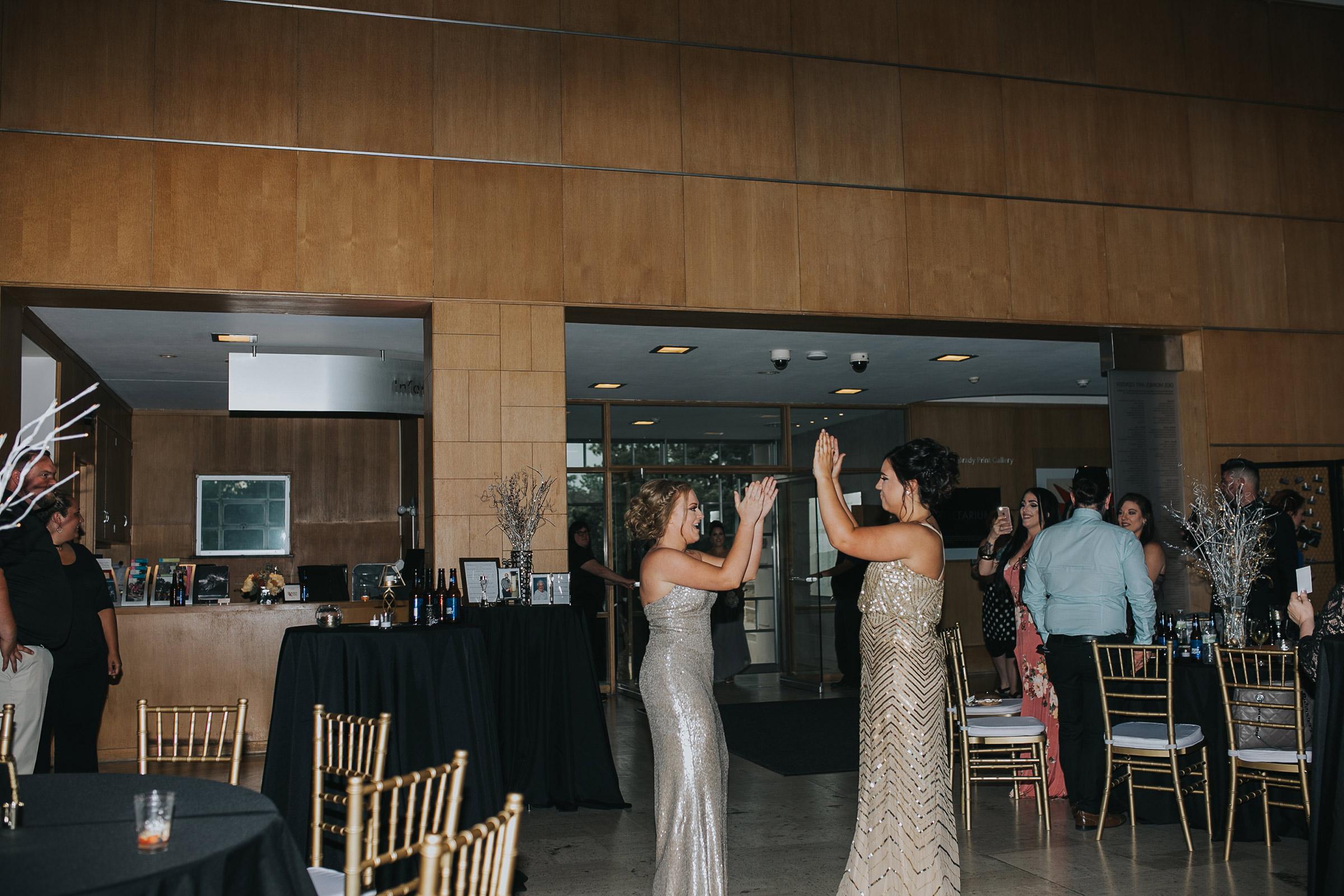 bridesmaids-grand-enterance-handshake-desmoines-iowa-art-center-raelyn-ramey-photography.jpg