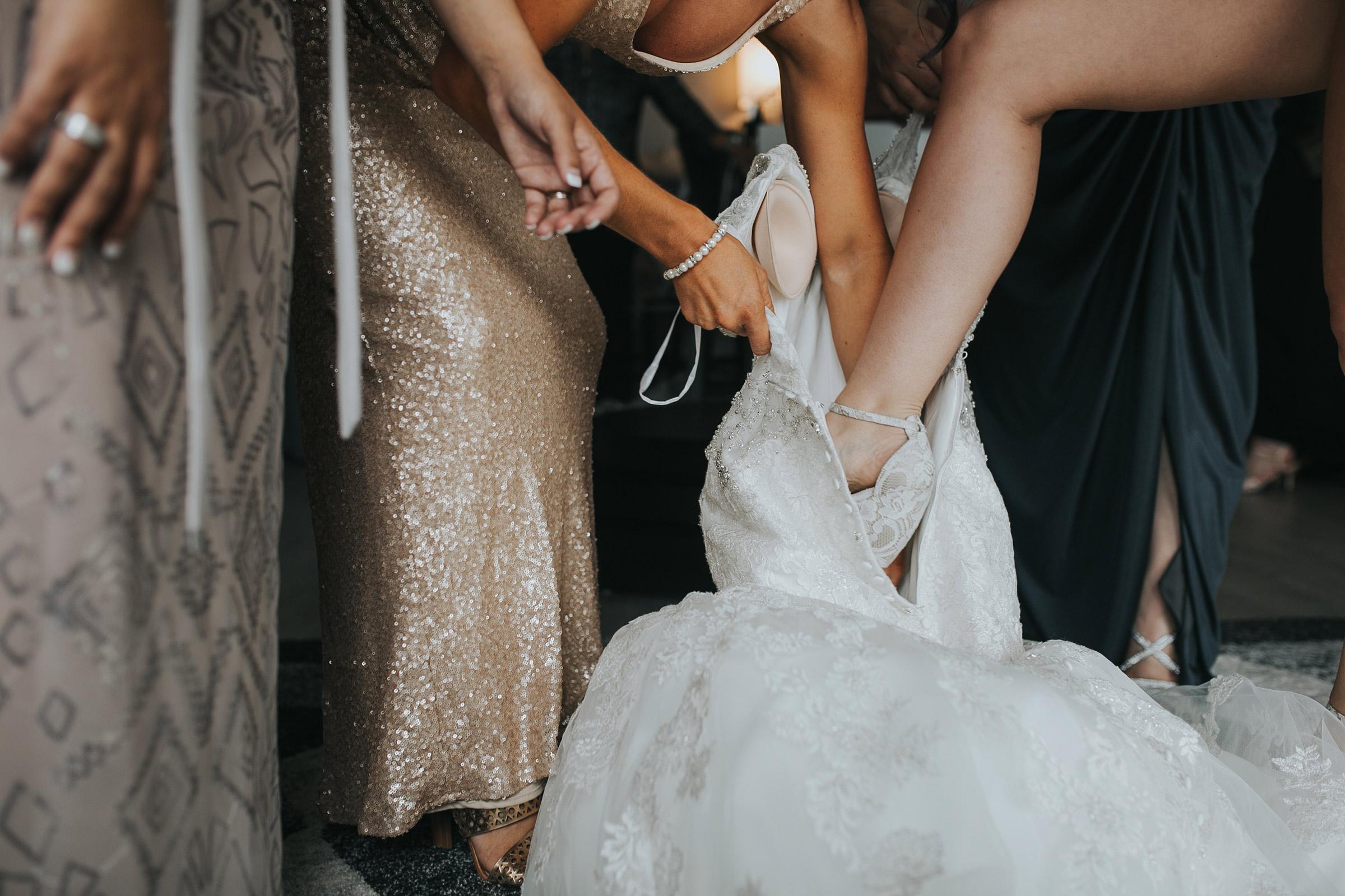 bridesmaids-helping-bride-step-into-dress-desmoines-iowa-ac-hotel-raelyn-ramey-photography.jpg
