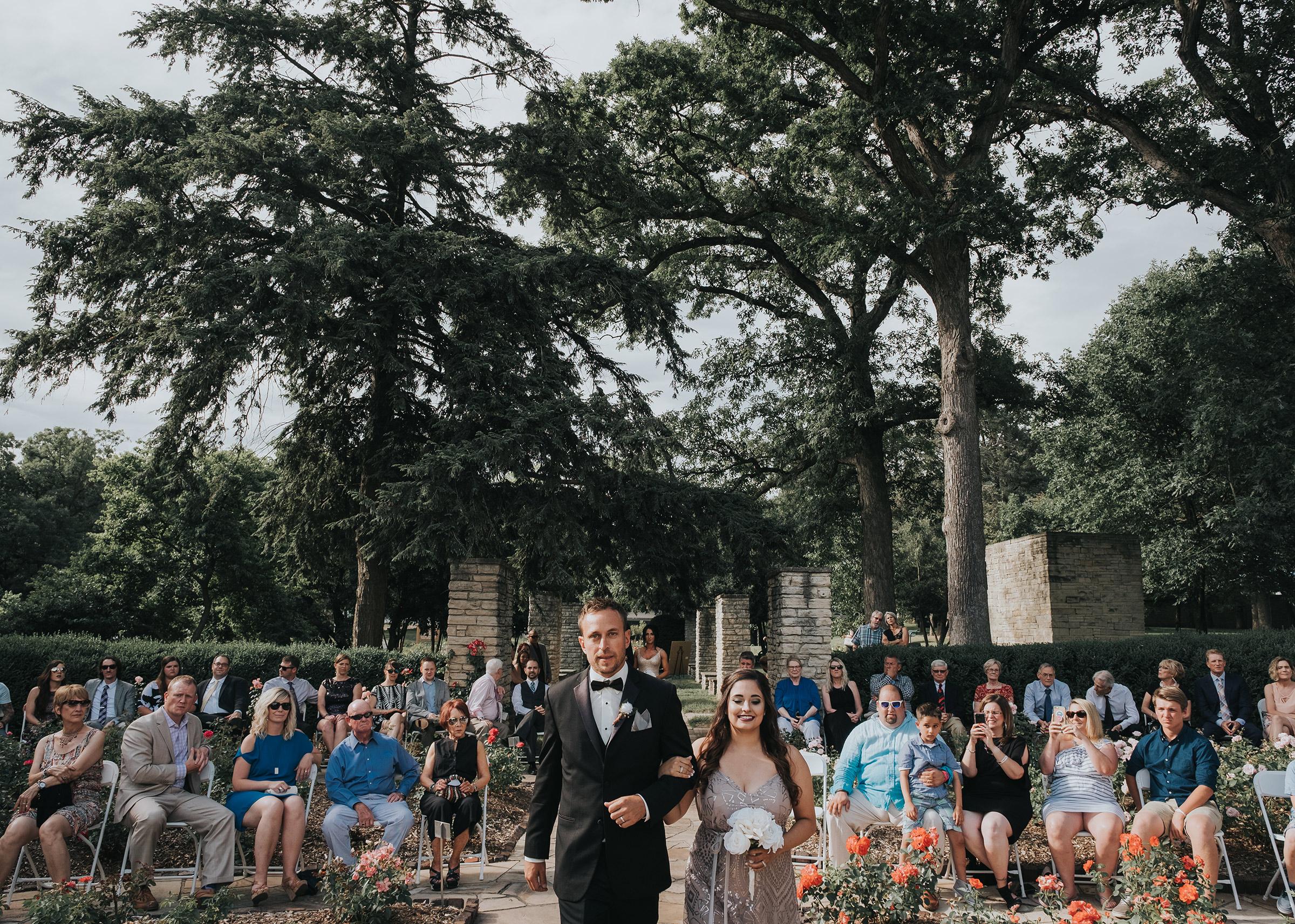 bridesmaids-groomsmen-walking-down-aisle-desmoines-iowa-rose-garden-raelyn-ramey-photography.jpg