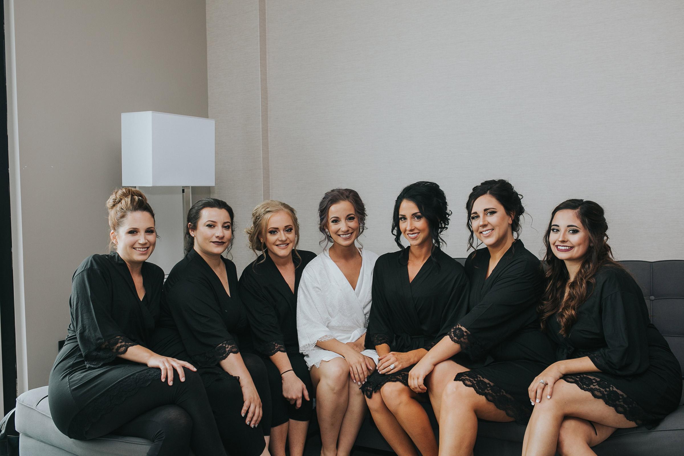bridesmaids-in-robes-posing-desmoines-iowa-ac-hotel-raelyn-ramey-photography.jpg