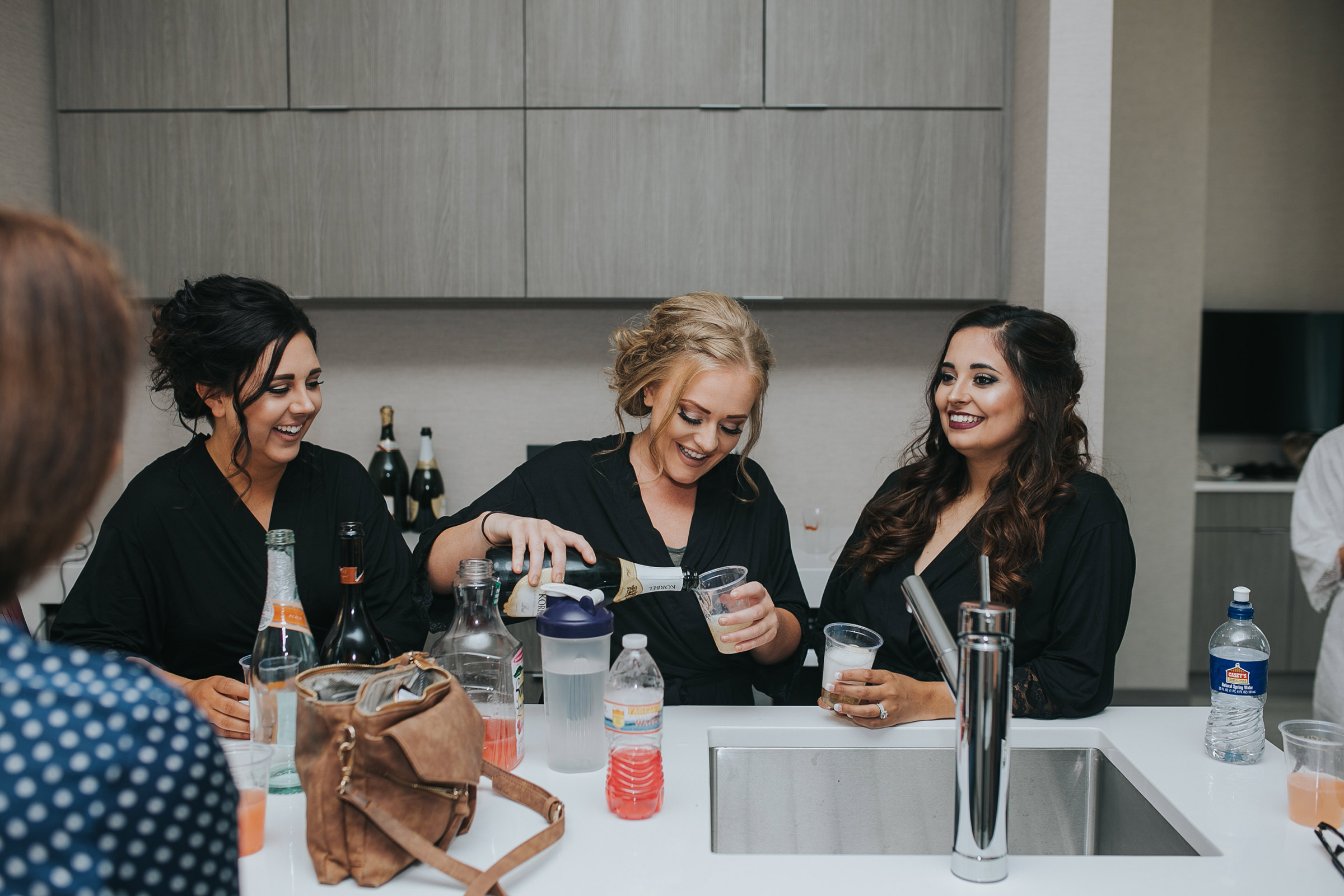 bridesmaids-pouring-drinks-desmoines-iowa-ac-hotel-raelyn-ramey-photography.jpg