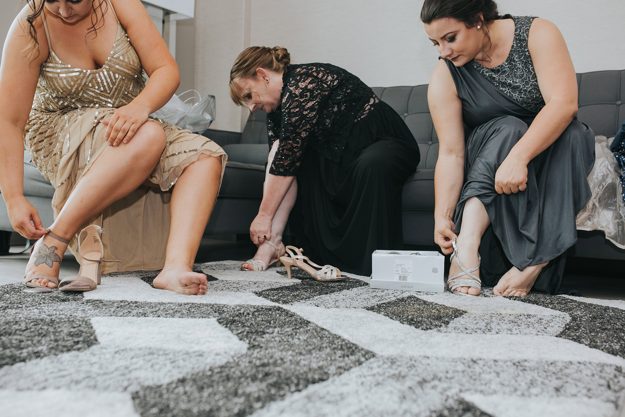 bridesmaids-putting-shoes-on-with-mother-of-bride-desmoines-iowa-ac-hotel-raelyn-ramey-photography.jpg