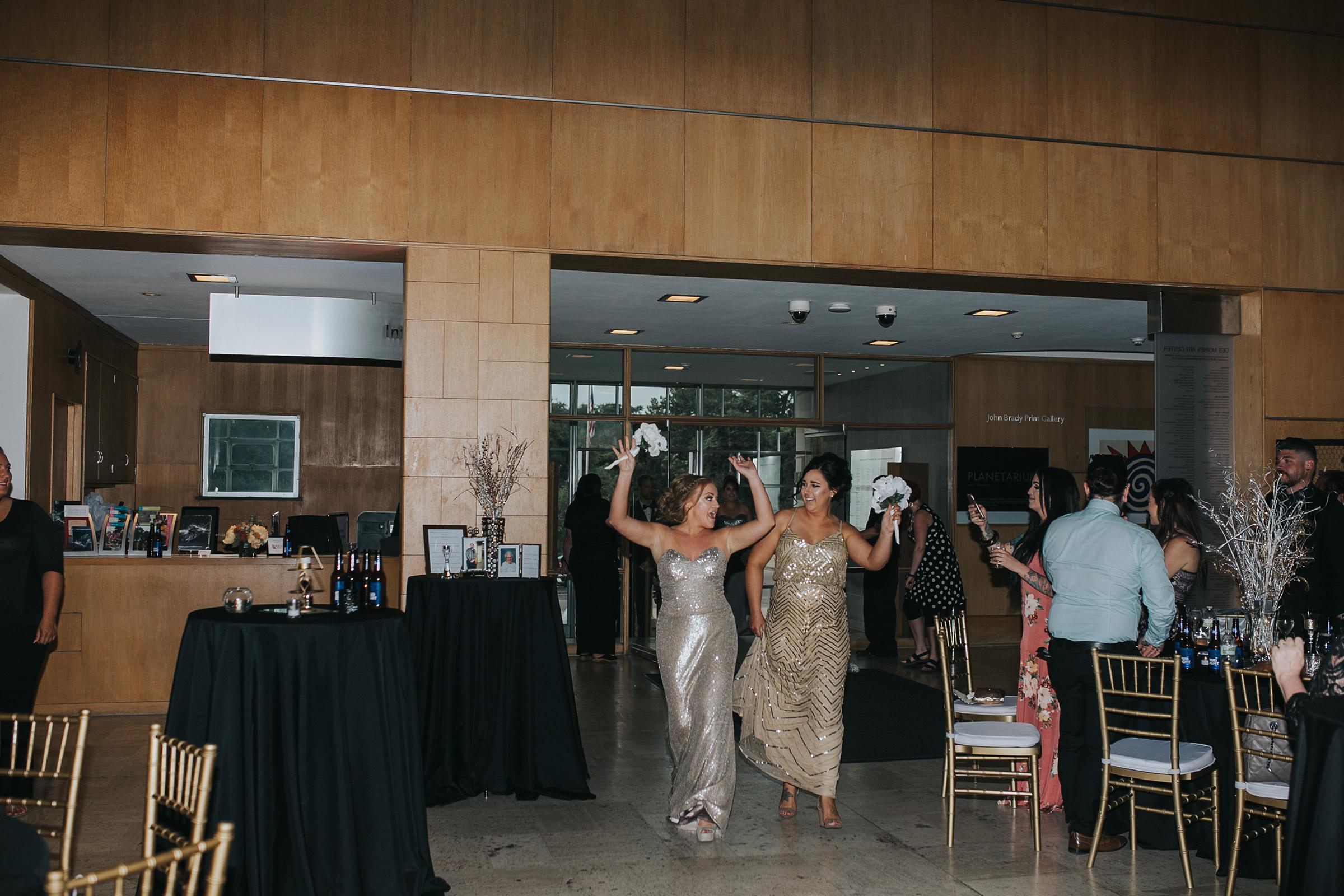 bridesmaids-skipping-grand-enterance-desmoines-iowa-art-center-raelyn-ramey-photography.jpg