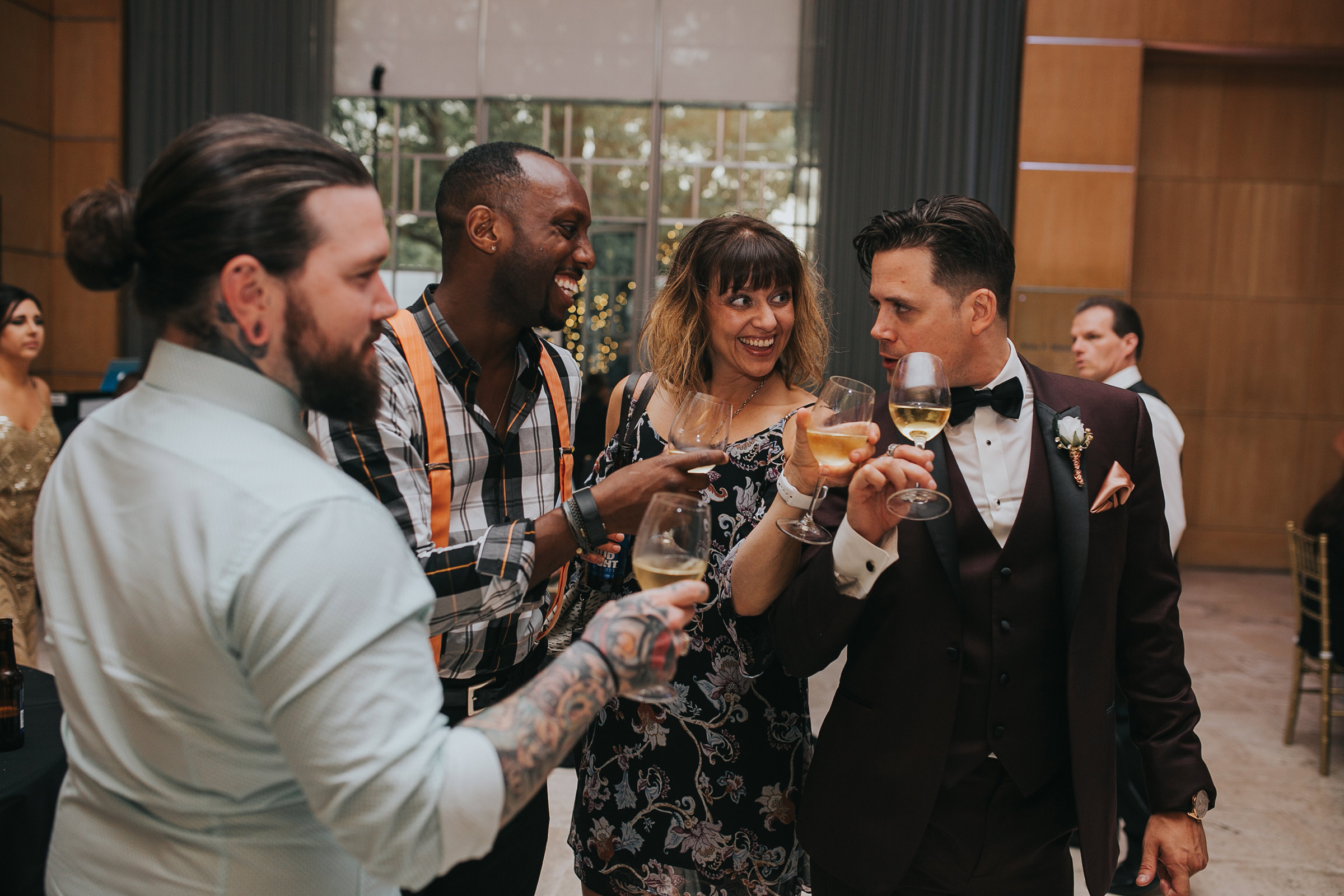 groom-cheersing-with-guests-and-posing-desmoines-iowa-art-center-raelyn-ramey-photography.jpg