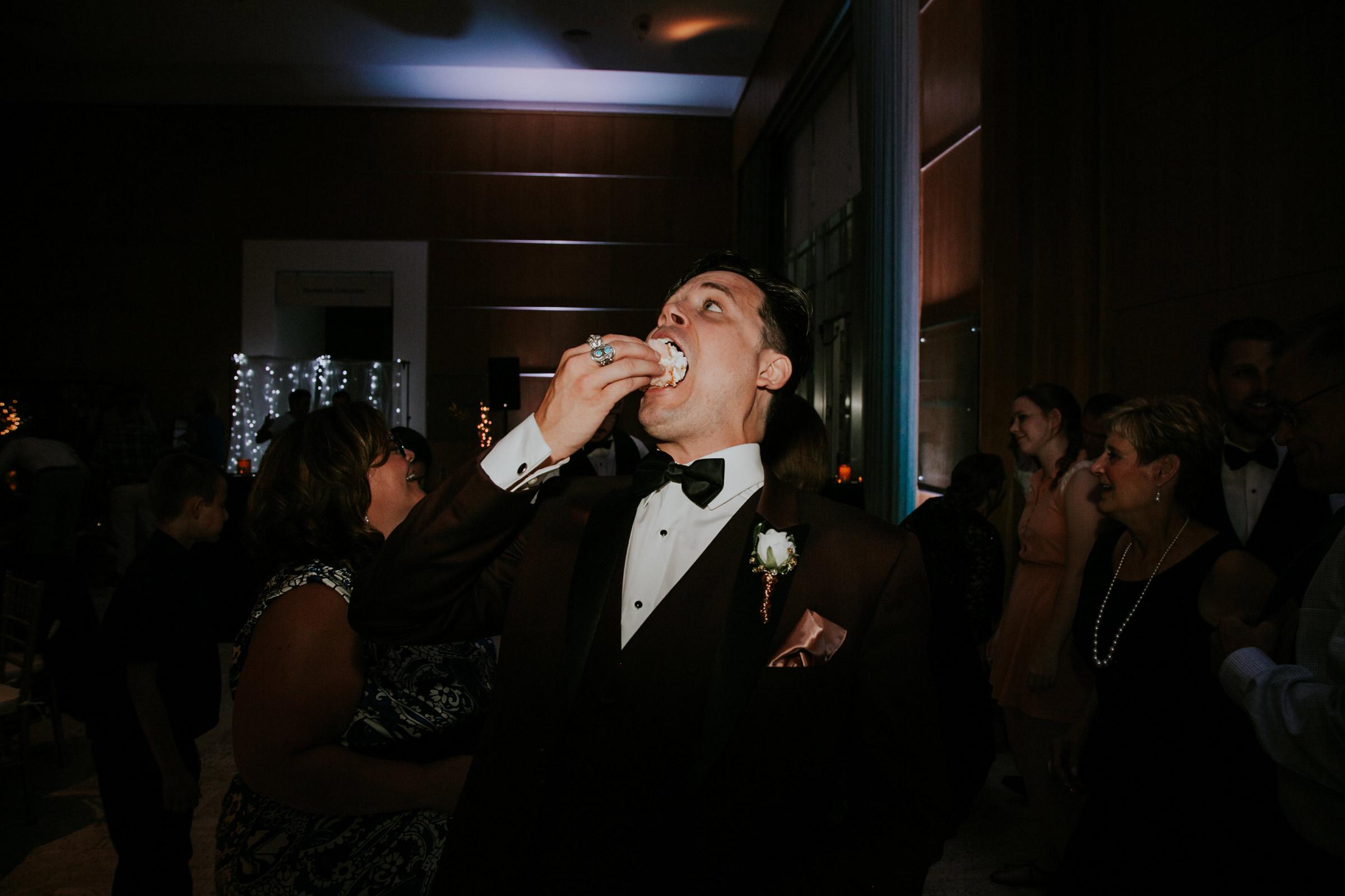groom-eating-cake-desmoines-iowa-art-center-raelyn-ramey-photography.jpg