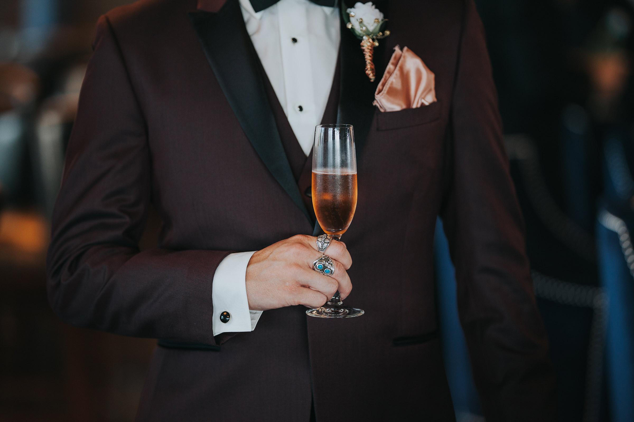 groom-holding-drink-republic-on-grand-desmoines-iowa-ac-hotel-raelyn-ramey-photography.jpg