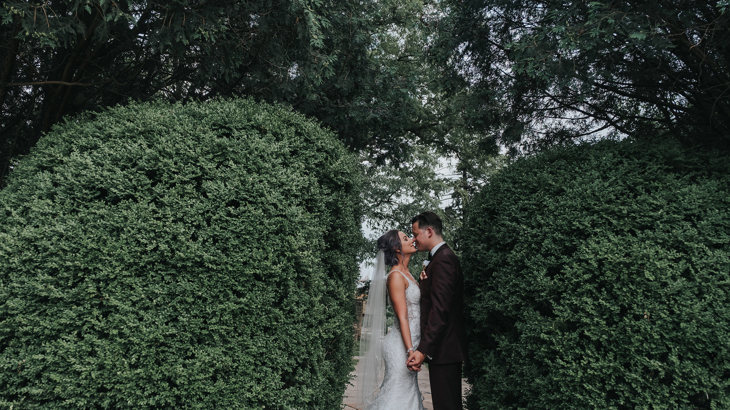 groom-kissing-bride-between-bushes-at-rose-garden-desmoines-iowa-art-center-raelyn-ramey-photography.jpg