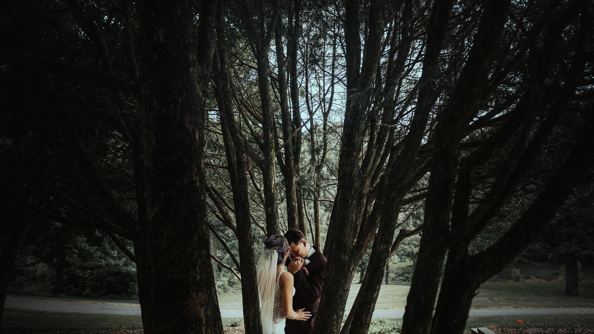 groom-kissing-brides-hand-in-rose-garden-desmoines-iowa-art-center-raelyn-ramey-photography.jpg
