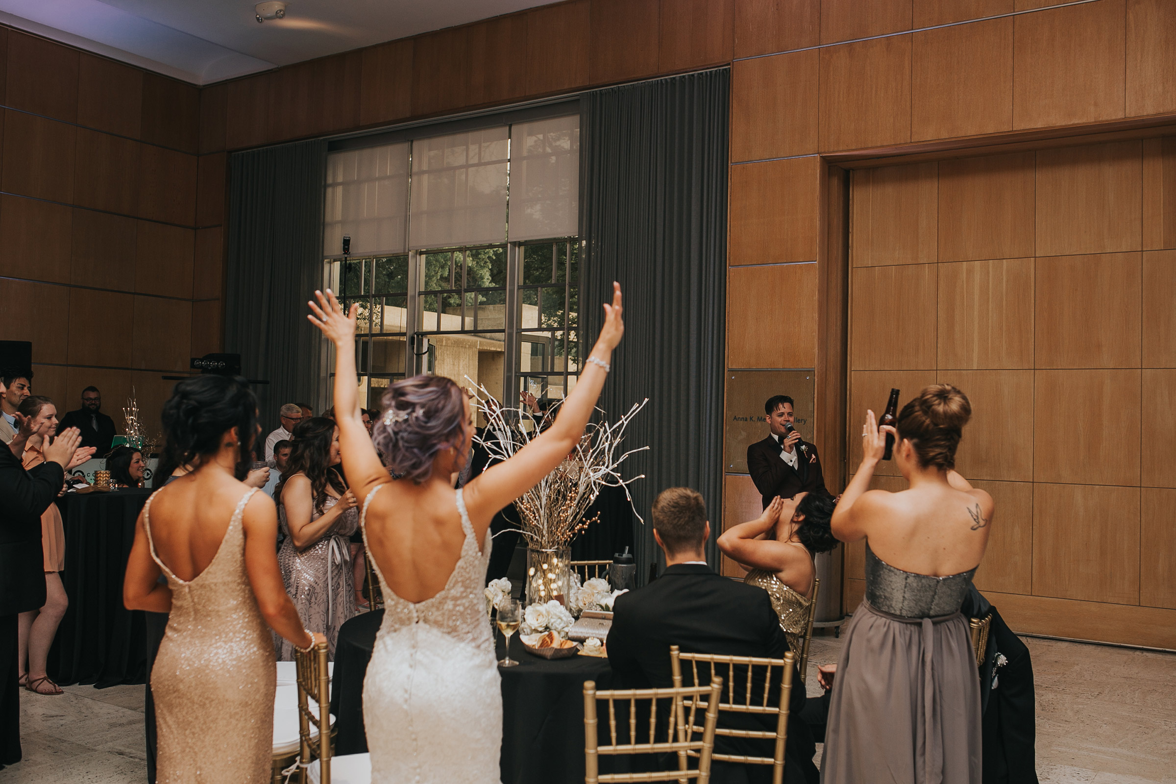 groom-making-speech-about-bride-with-her-hands-in-the-air-desmoines-iowa-art-center-raelyn-ramey-photography.jpg