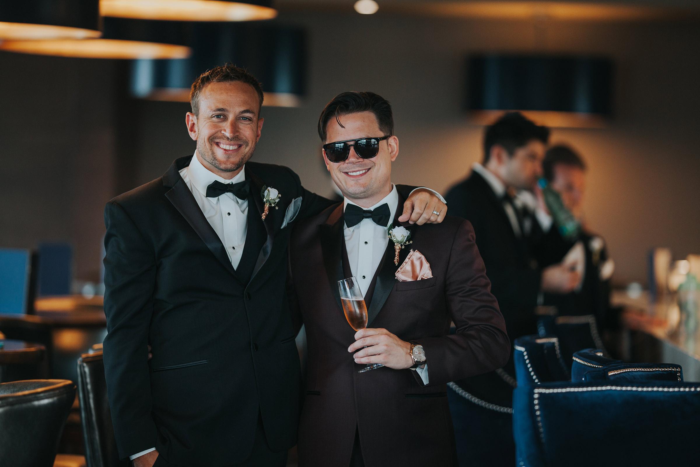 groom-posing-with-groomsmen-at-republic-on-grand-desmoines-iowa-ac-hotel-raelyn-ramey-photography.jpg