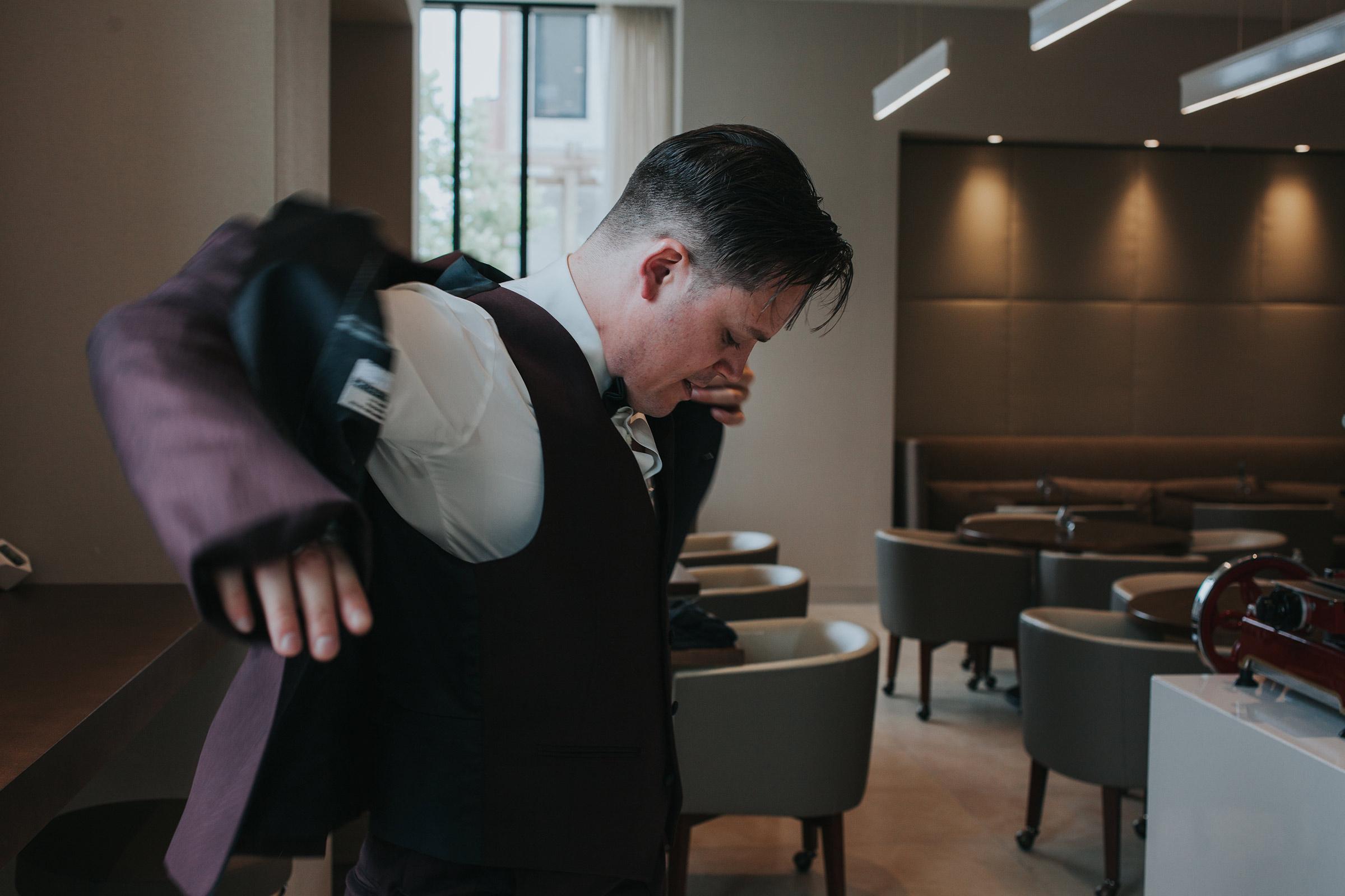 groom-putting-suite-jacket-on-desmoines-iowa-ac-hotel-raelyn-ramey-photography.jpg