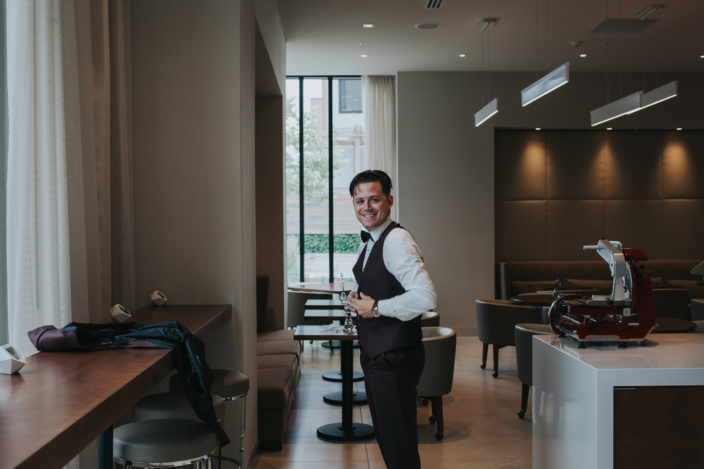 groom-putting-vest-on-desmoines-iowa-ac-hotel-raelyn-ramey-photography.jpg