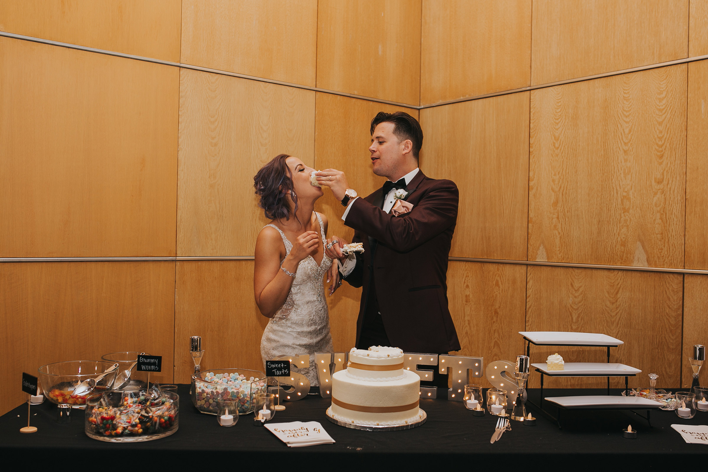groom-shoved-cake-in-brides-face-cake-cutting-desmoines-iowa-art-center-raelyn-ramey-photography.jpg