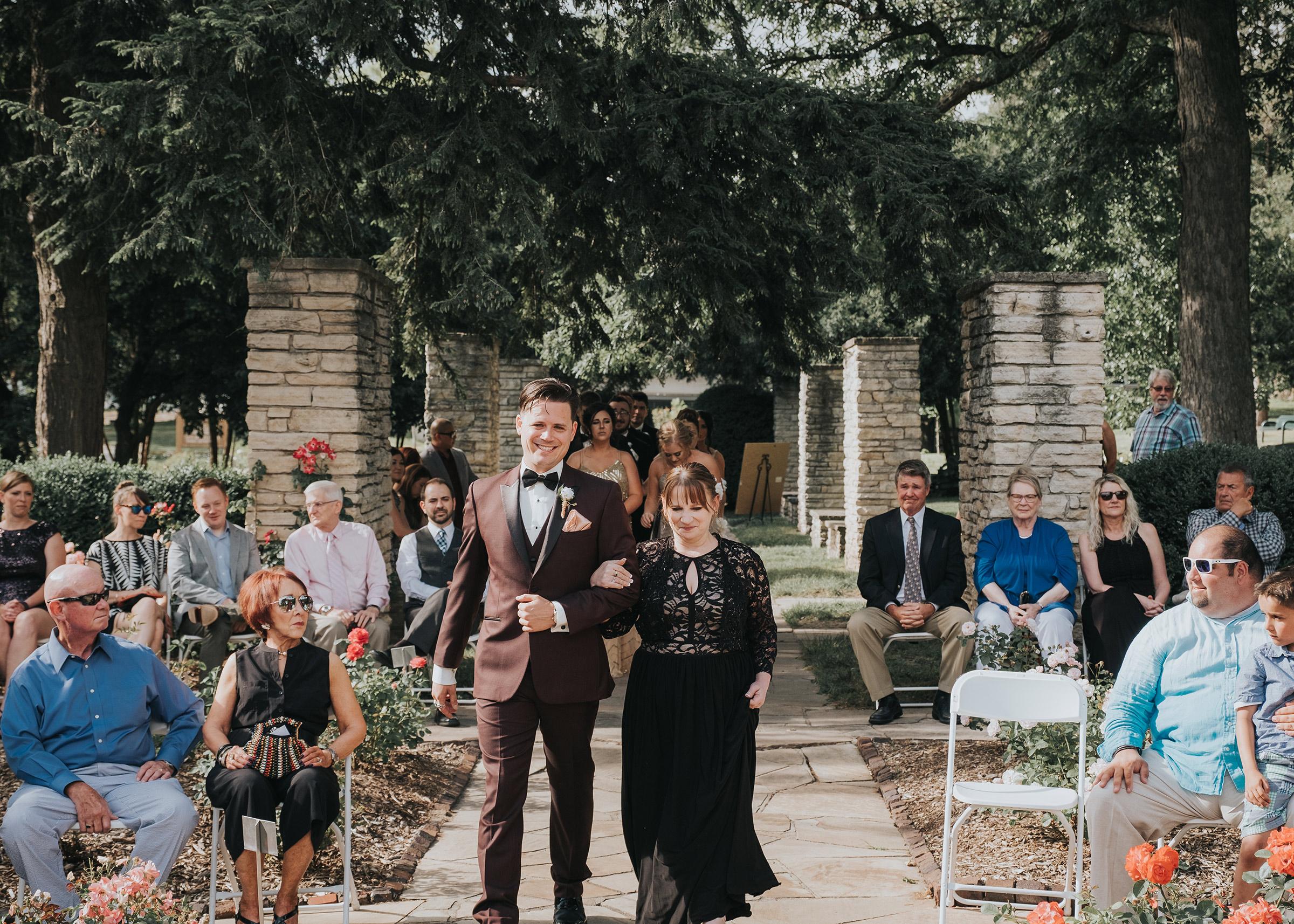 groom-walking-brides-mother-down-aisle-desmoines-iowa-rose-garden-raelyn-ramey-photography.jpg