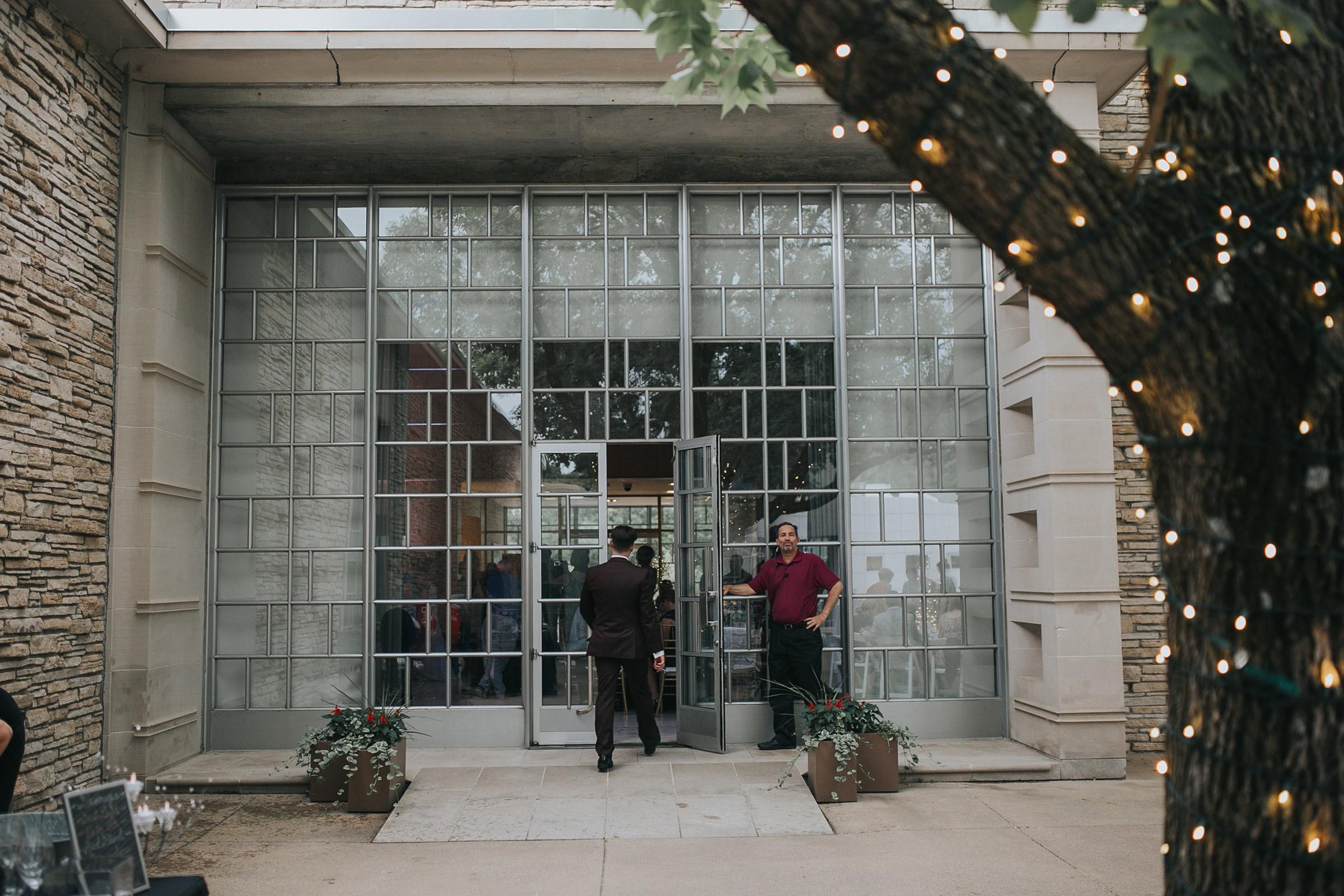 groom-walking-into-reception-from-courtyard-desmoines-iowa-art-center-raelyn-ramey-photography.jpg