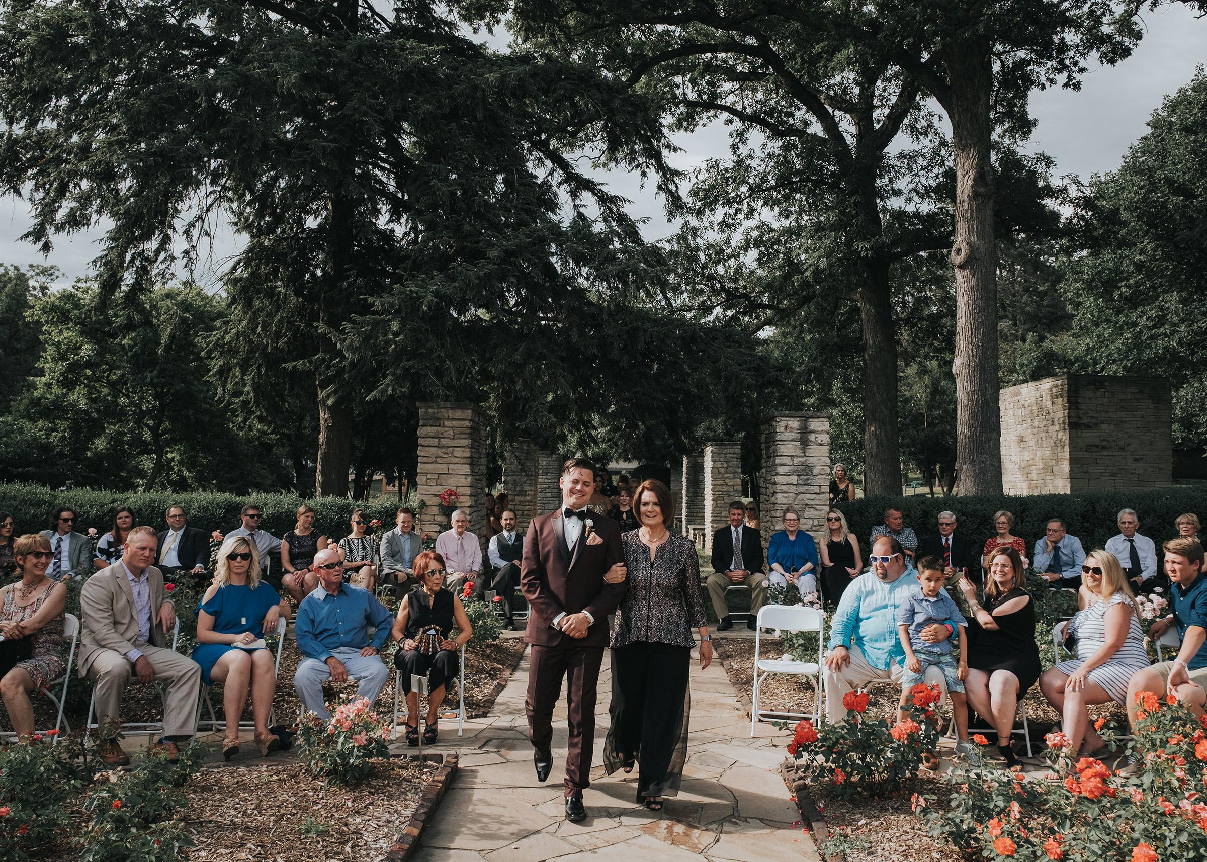 groom-walking-mother-down-aisle-desmoines-iowa-rose-garden-raelyn-ramey-photography.jpg