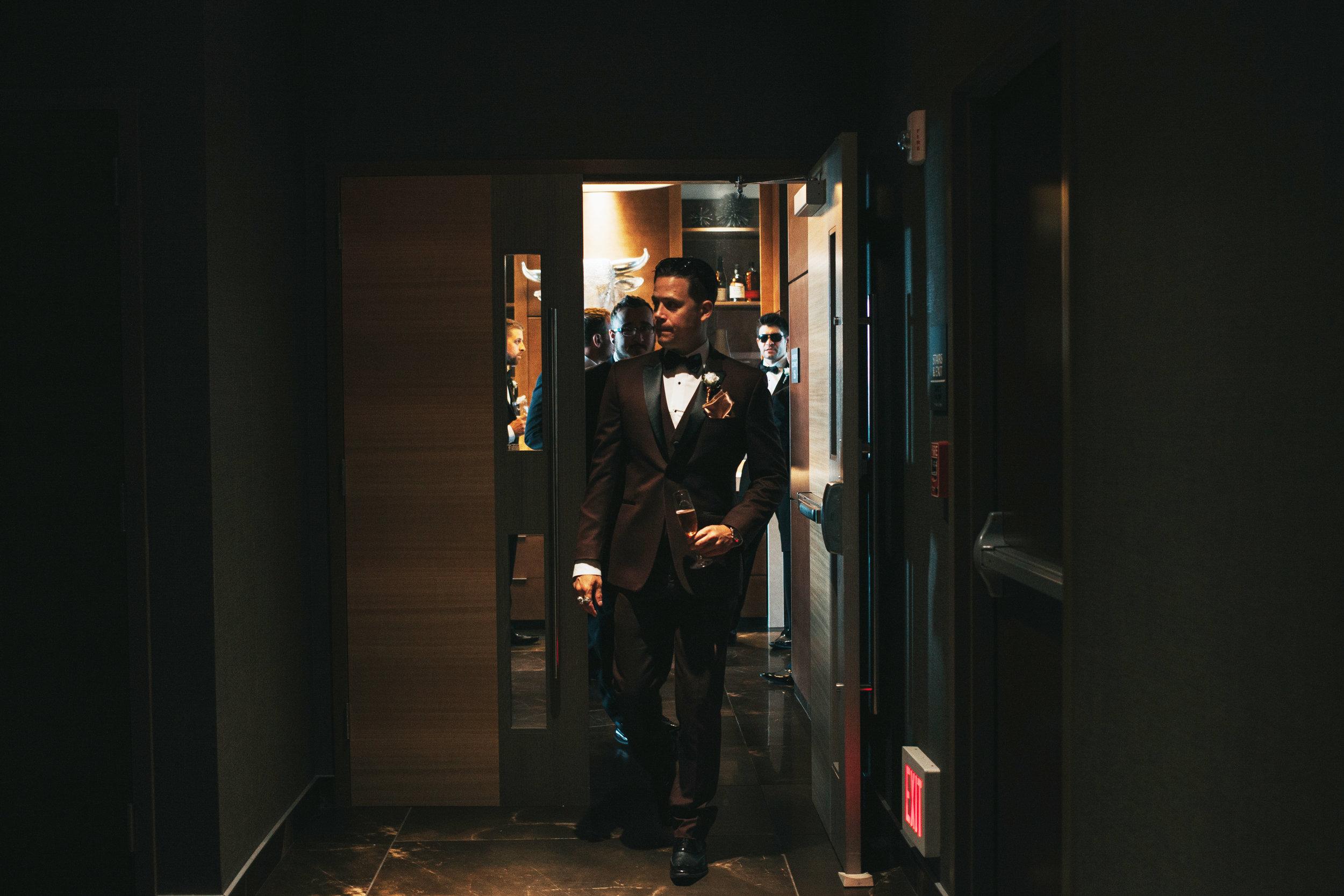 groom-walking-out-of-republic-on-grand-desmoines-iowa-ac-hotel-raelyn-ramey-photography.jpg