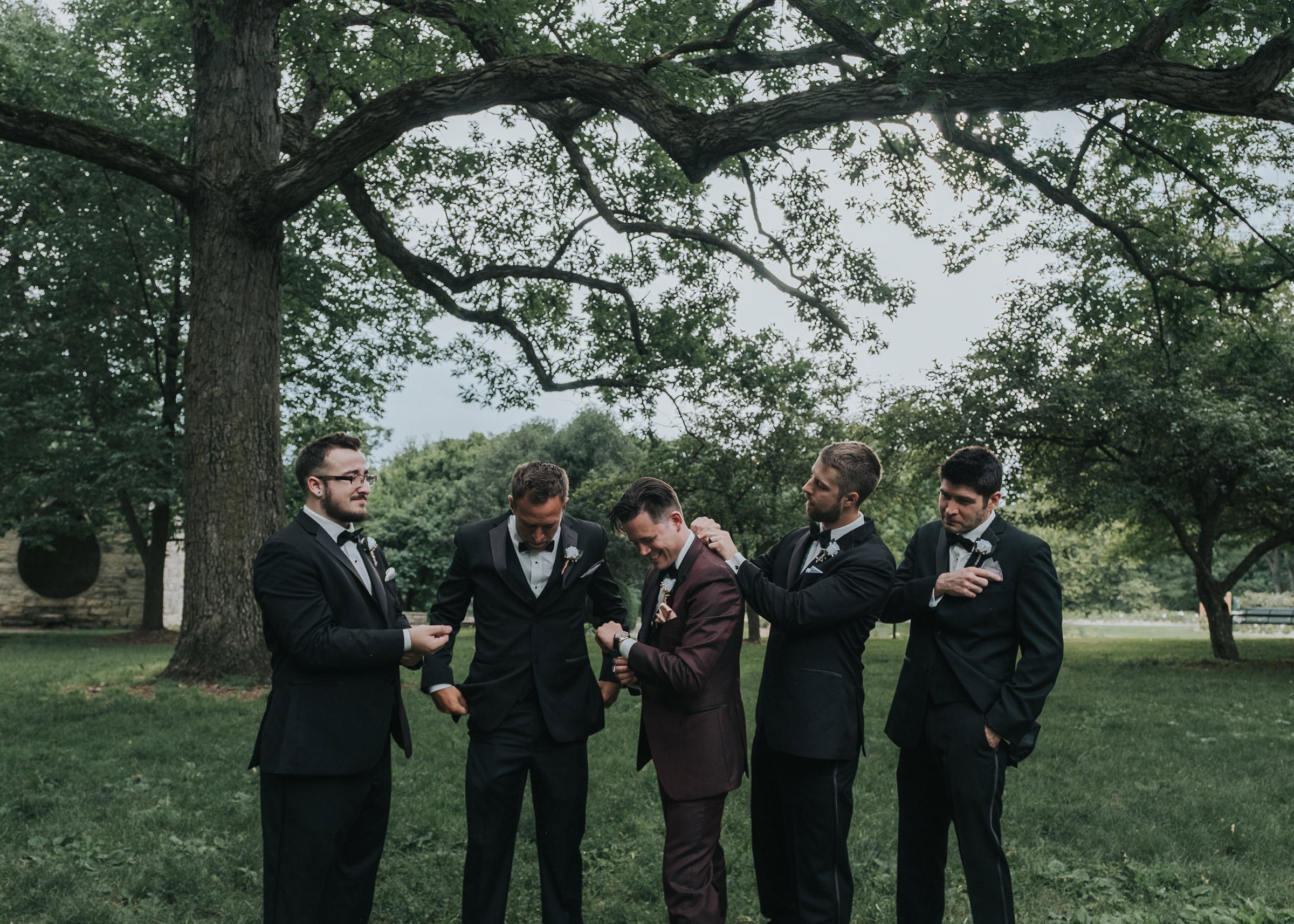 groomsmen-helping-groom-fix-clothing-desmoines-iowa-art-center-raelyn-ramey-photography.jpg