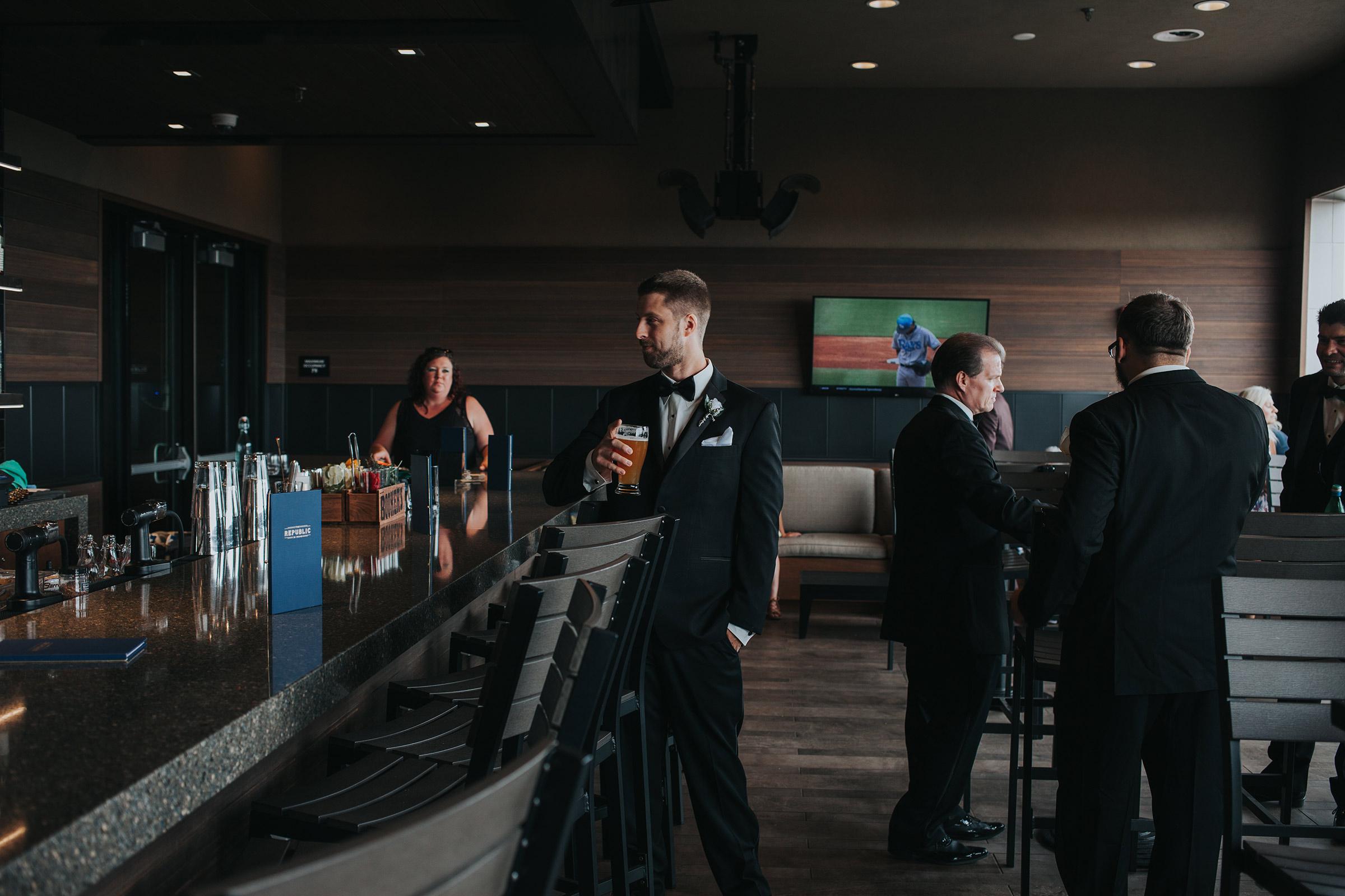 groomsmen-ording-drink-at-bar-republic-on-grand-desmoines-iowa-ac-hotel-raelyn-ramey-photography.jpg