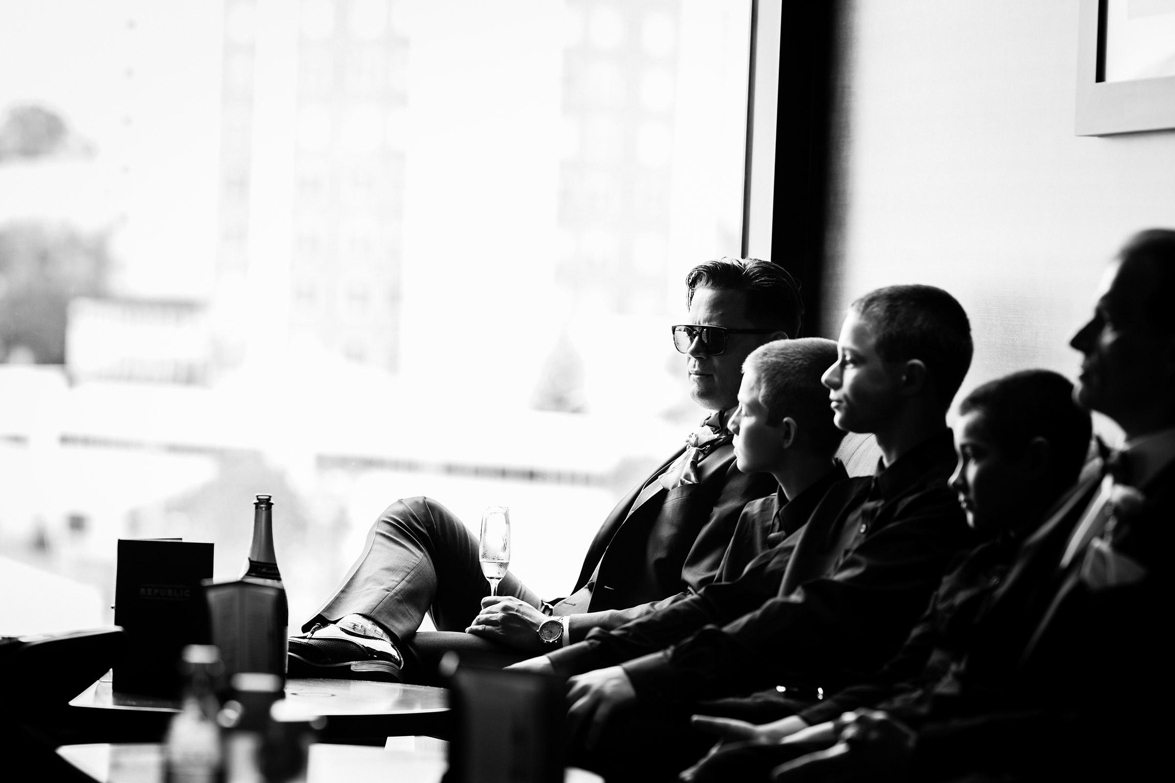 groomsmen-sitting-in-chair-at-republic-on-grand-desmoines-iowa-ac-hotel-raelyn-ramey-photography.jpg