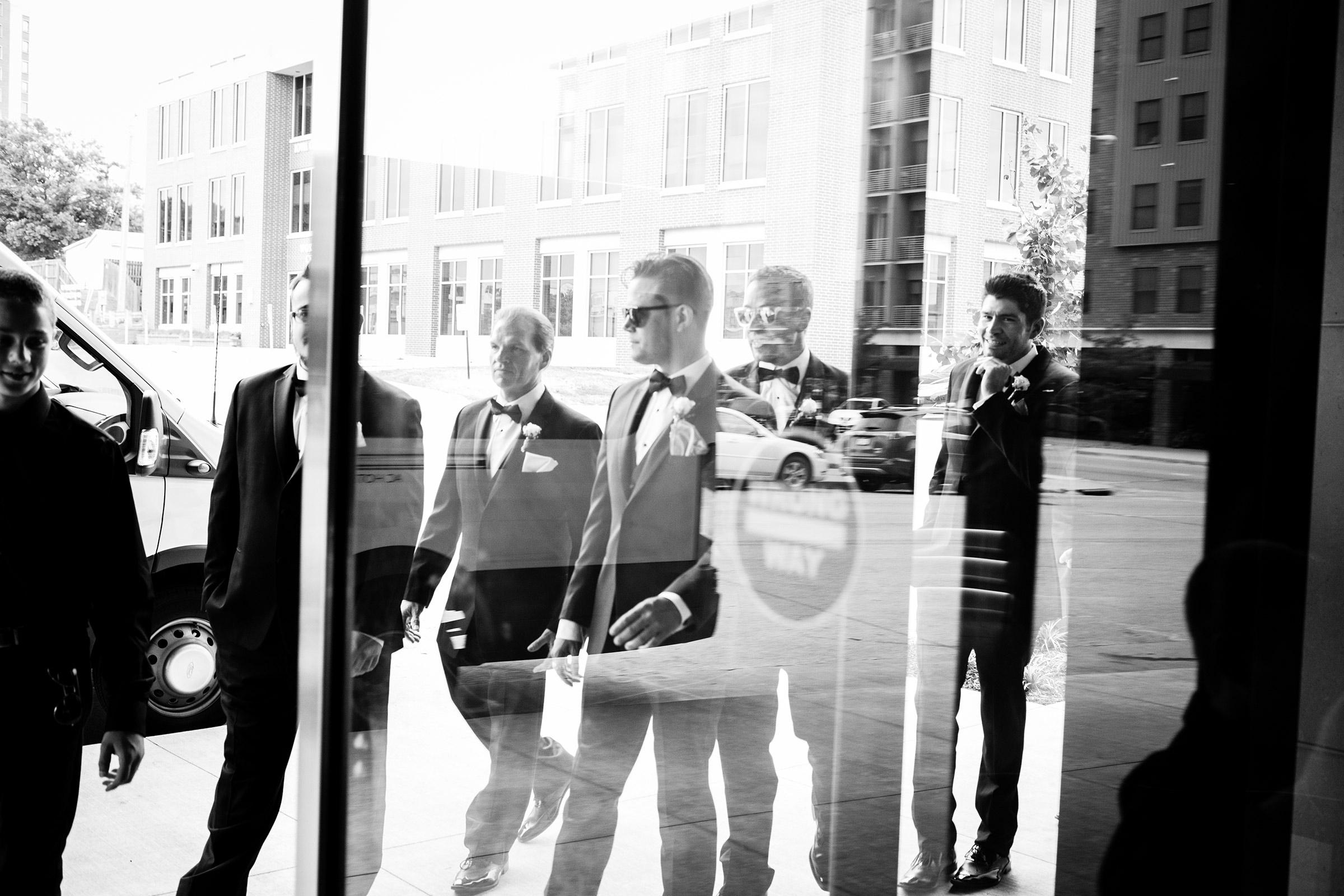 groomsmen-walking-outside-desmoines-iowa-ac-hotel-raelyn-ramey-photography.jpg